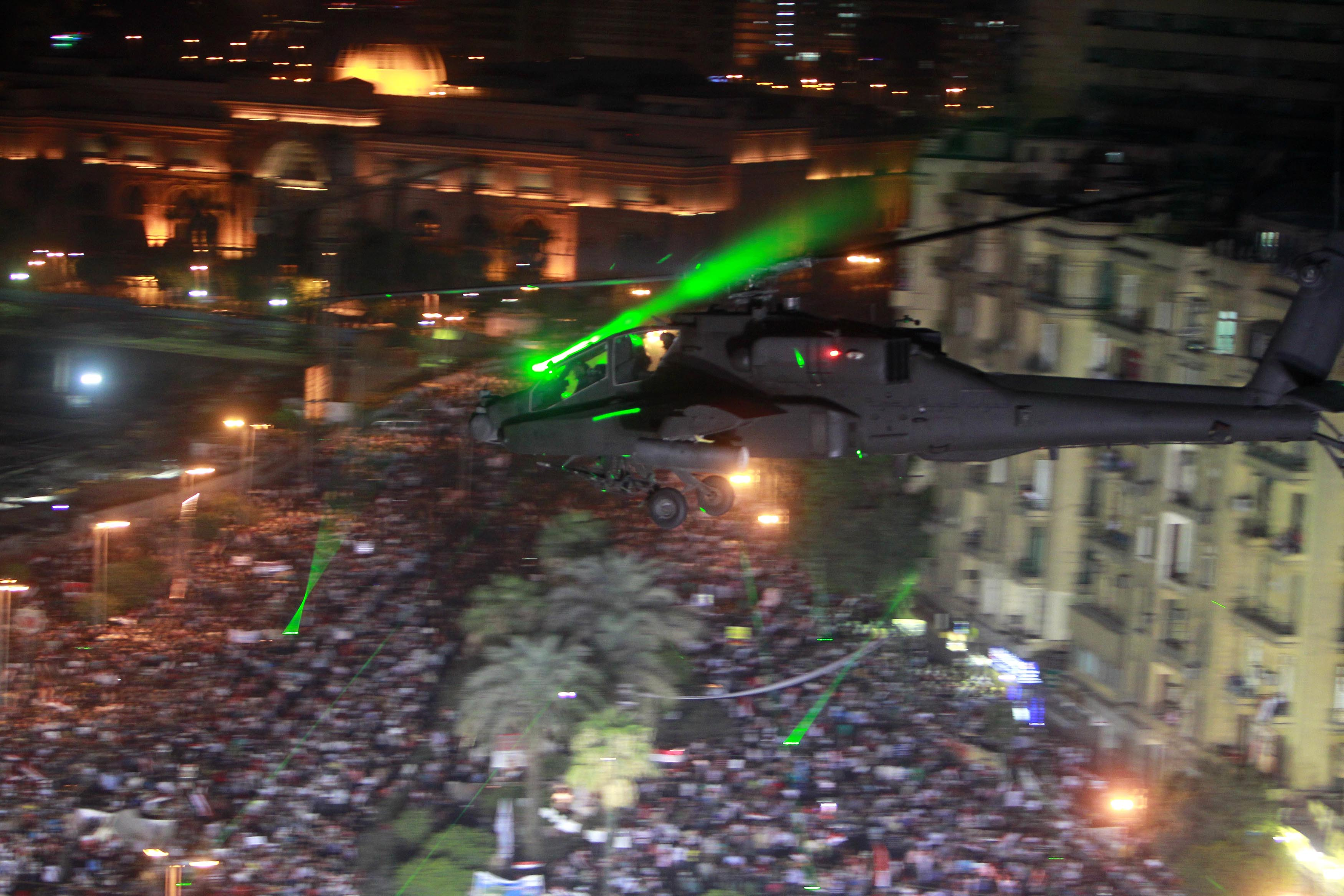An AH-64 Apache helicopter flies over Cairo's Tahrir Square in 2013.