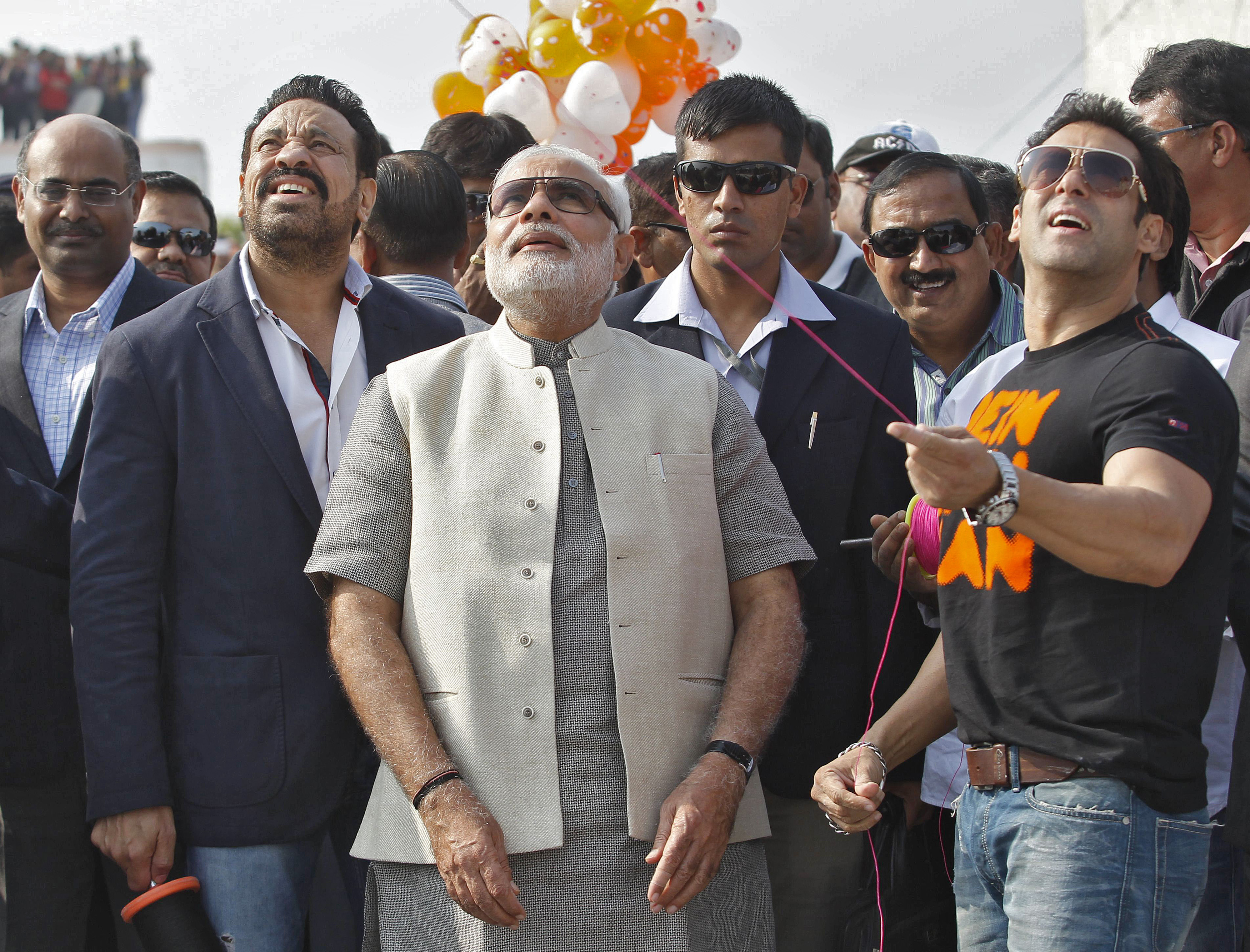 Bollywood actor Salman Khan (R) flies a kite as Hindu nationalist Narendra Modi (C), prime ministerial candidate for India's main opposition Bharatiya Janata Party (BJP) and Gujarat's chief minister, watches during a kite flying festival in the western Indian city of Ahmedabad January 14, 2014.