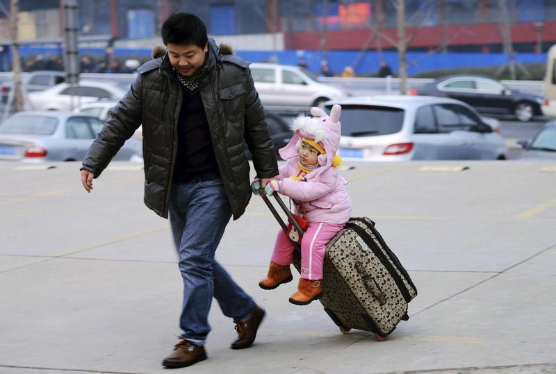 A man drags a suitcase with a girl sitting on it at a bus terminus in China on Jan. 16, 2014
