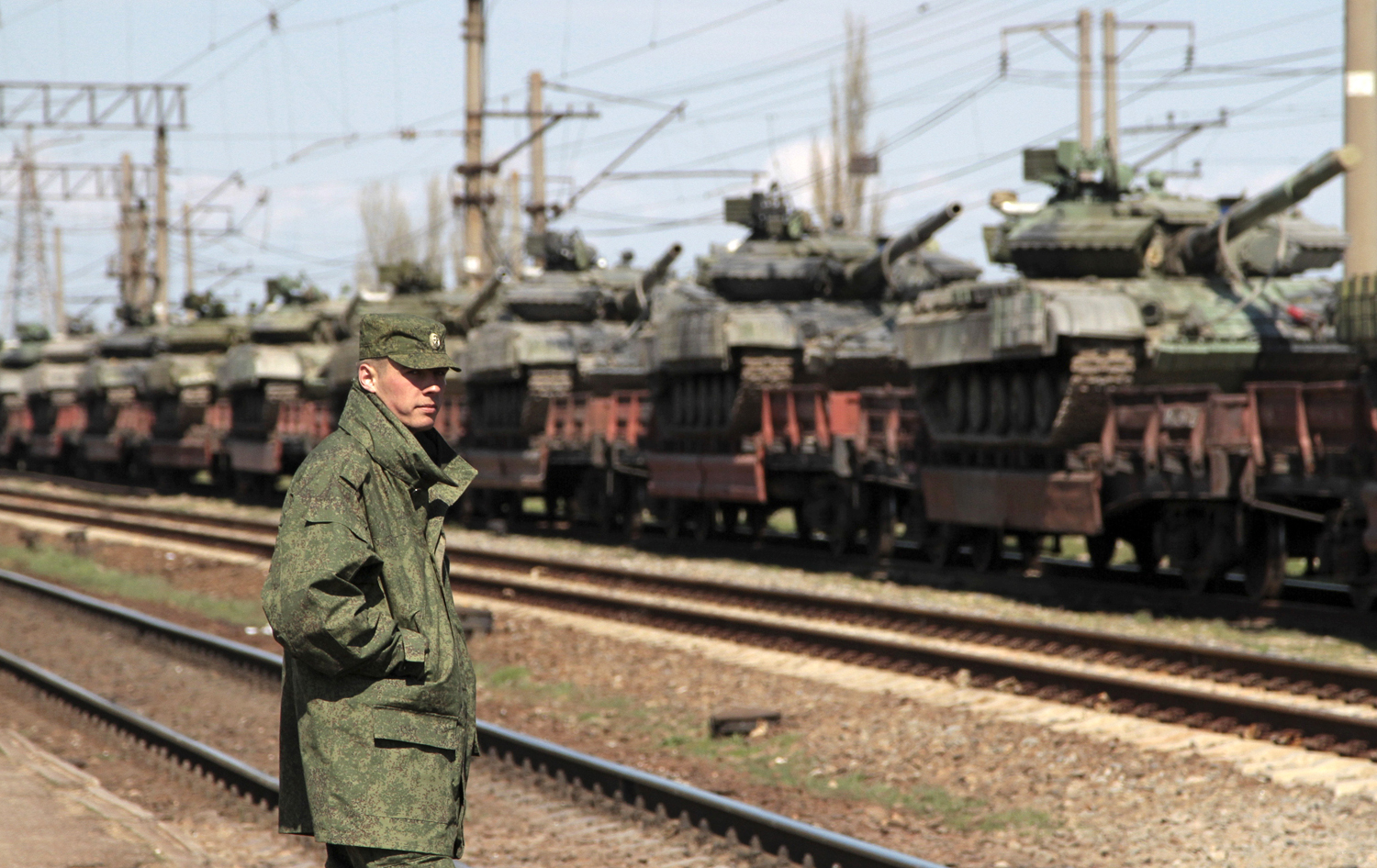 A Russian serviceman stands near Ukrainian tanks on freight cars before departing from Crimea