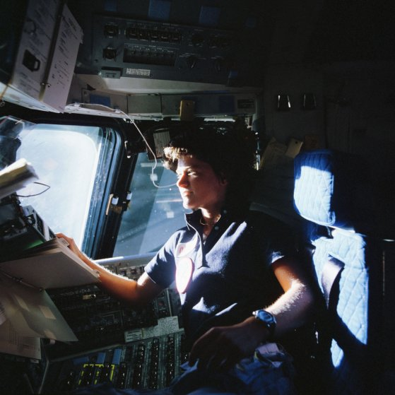NASA Astronaut Sally K. Ride, STS-7 mission specialist, communicates with ground controllers from the flight deck of the Earth-orbiting Space Shuttle Challenger at an unknown location, on June 21, 1983. Ride was America's first woman in space.