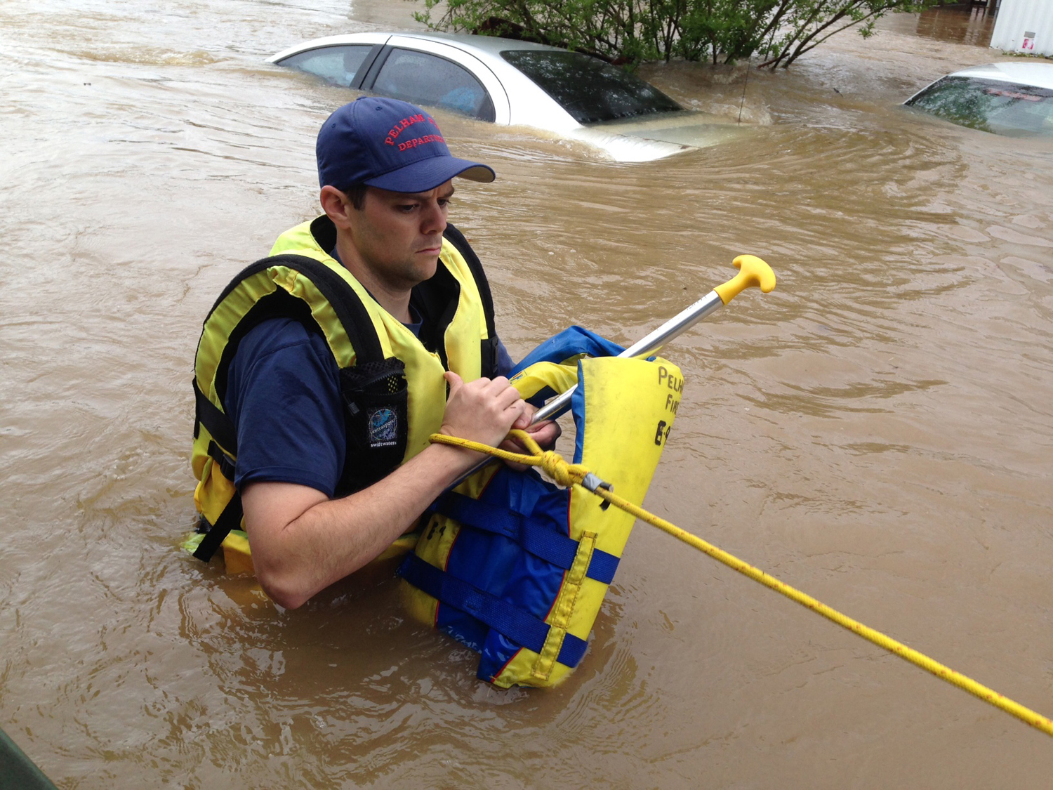 Firefighter Rusty Murphy wades through flood waters in a mobile home park in Pelham, Ala., on Monday, April 7, 2014.