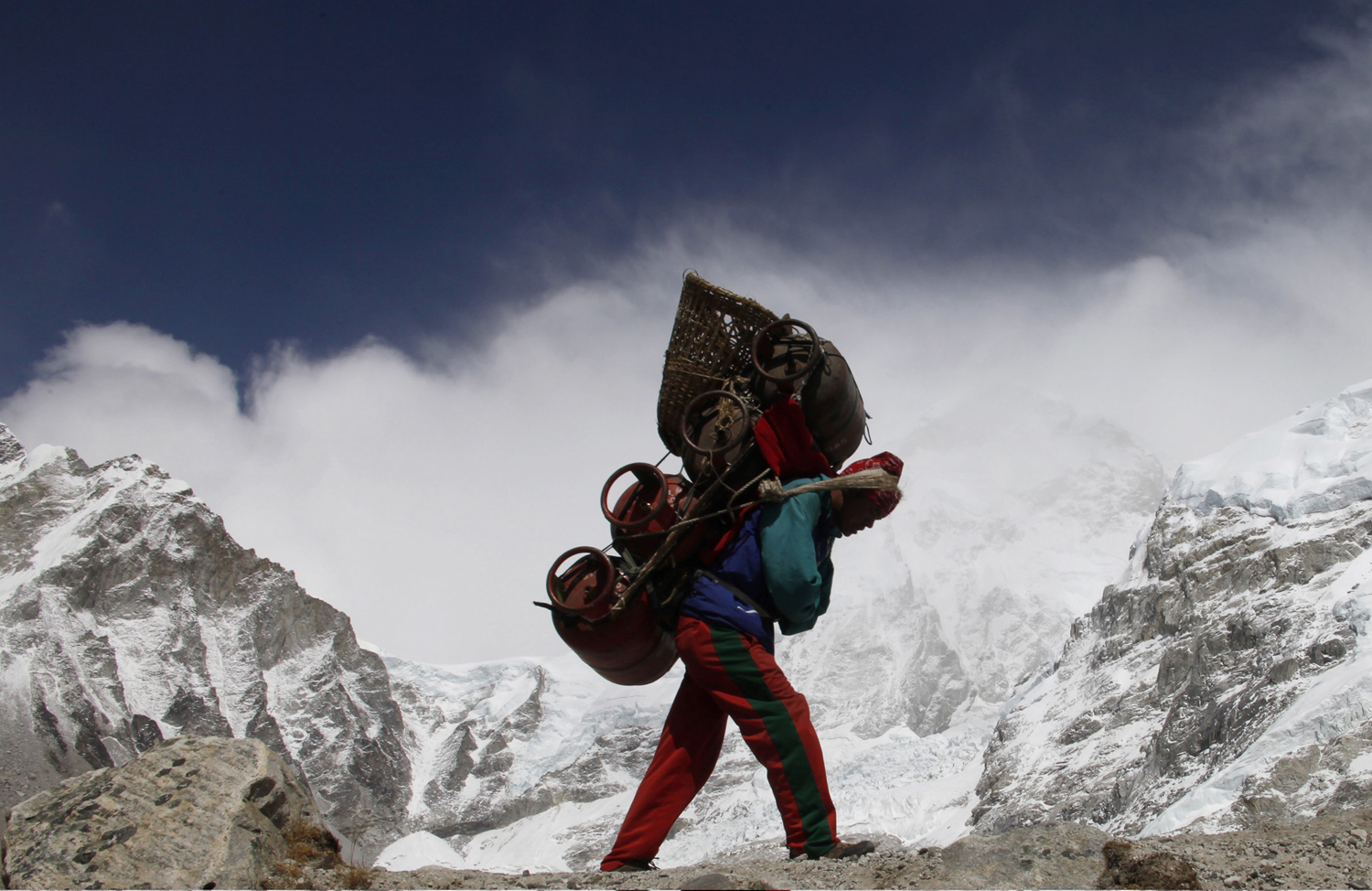 A Nepalese porter walks with his load from Everest base camp in Nepal on May 3, 2011