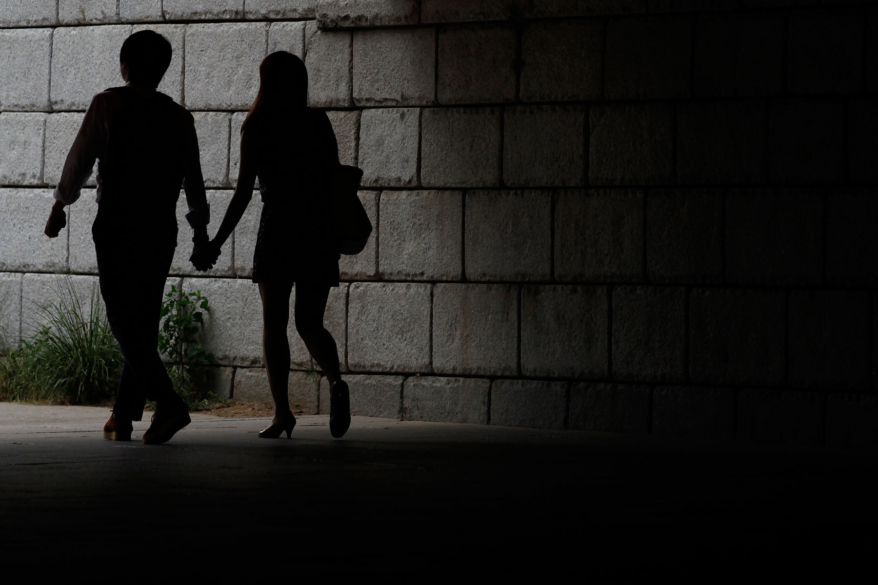 A couple walks while holding hands under a bridge in central Seoul