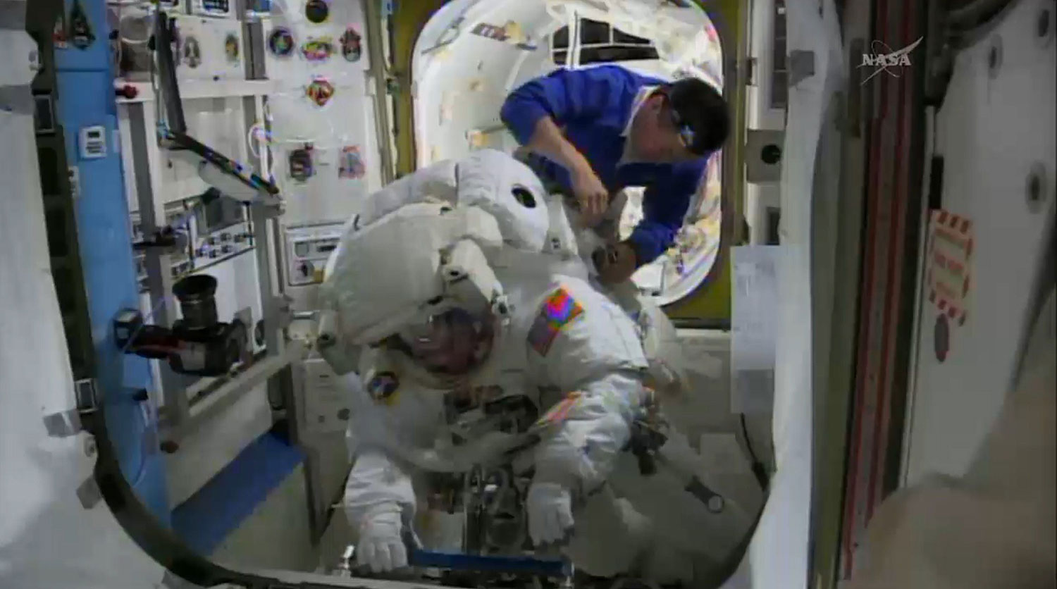 This April 23, 2014 NASA TV image shows International Space Station(ISS) astronauts Koichi Wakata of Japan as he helps Rick Mastracchio of the US(front) prepare for a spacewalk to install a backup computer that failed earlier this month.