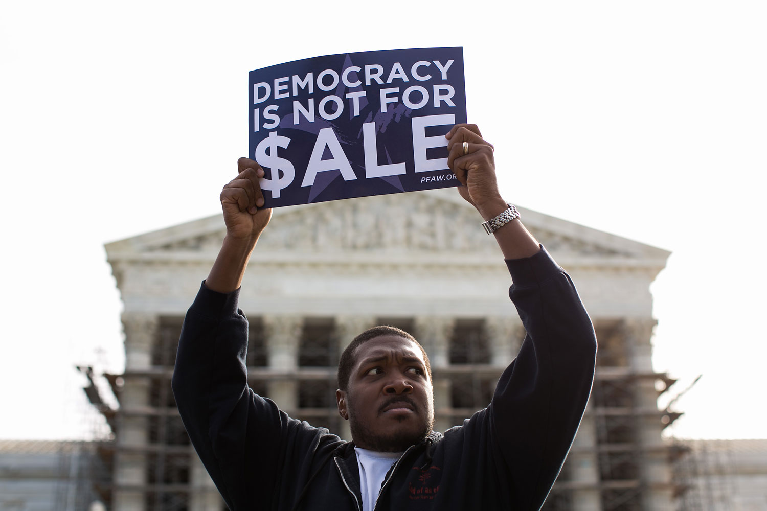 Cornell Woolridge holds a sign as he rallies against money in politics, at the Supreme Court in Washington, on October 8, 2013 in Washington, DC.