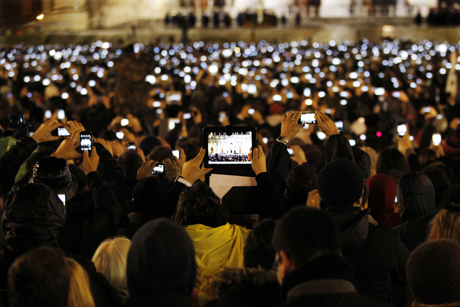 Visitors take photos of Pope Francis as he speaks from the central balcony of St. Peter's Basilica at the Vatican.