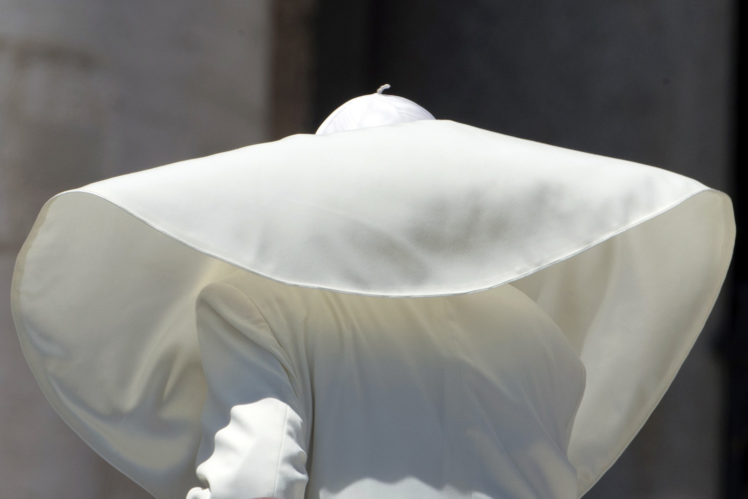 A gust of wind blows the pope's mantle.