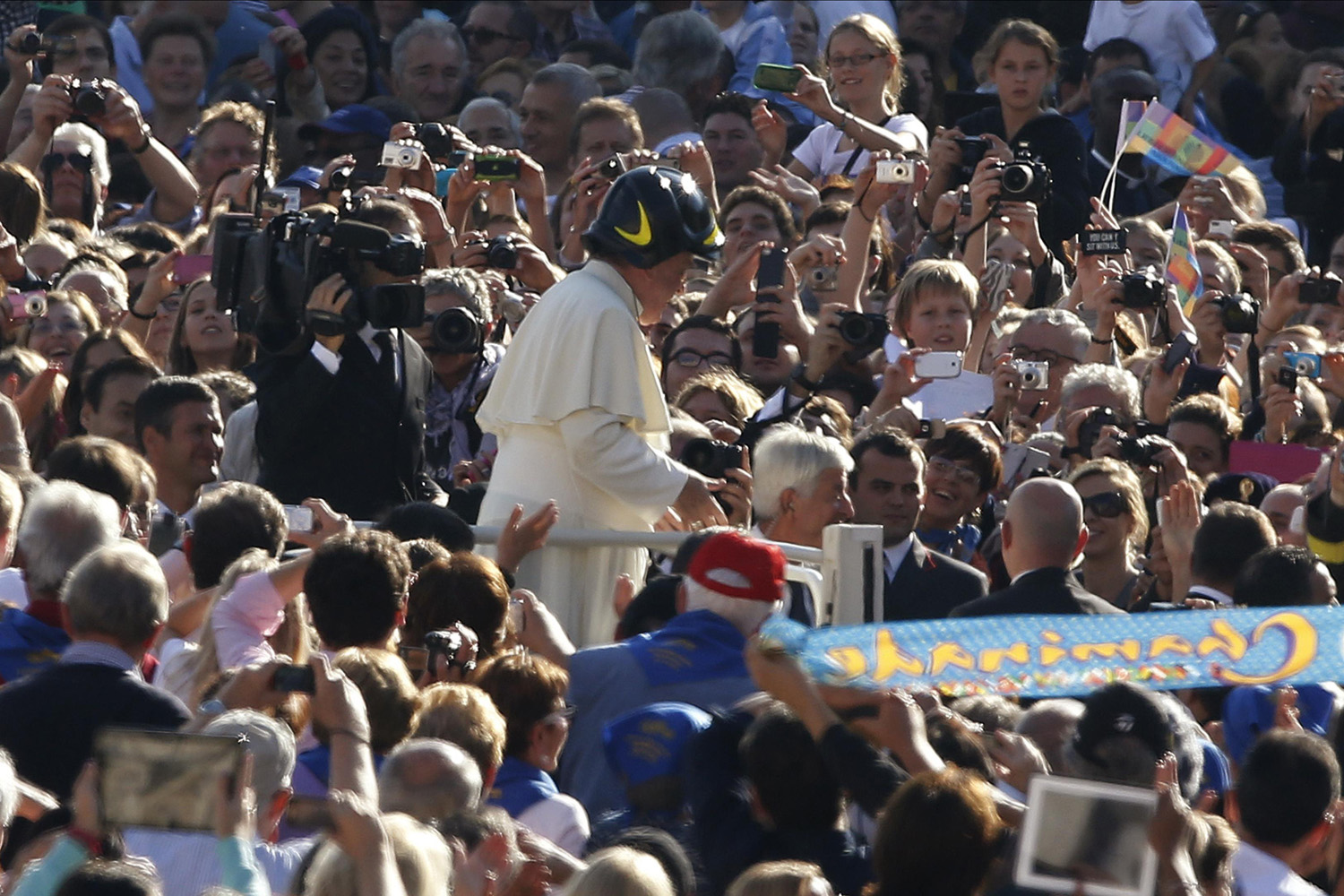 Arriving to lead his General Audience in a firefighter's helmet.
