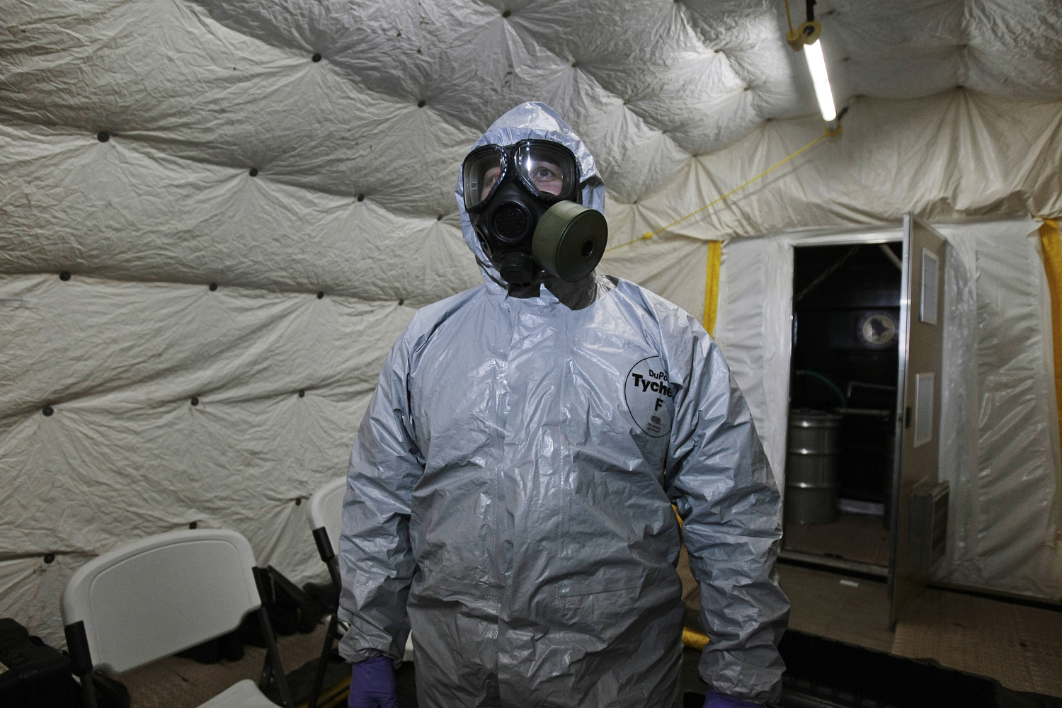 A marine officer of the Cape Ray, a ship equipped to neutralize Syrian chemicals, shows a chemical protection suit  to reporters during a tour around the ship docked at the naval base of Rota used by the U.S, in Spain's southwestern coast on April 10, 2014.