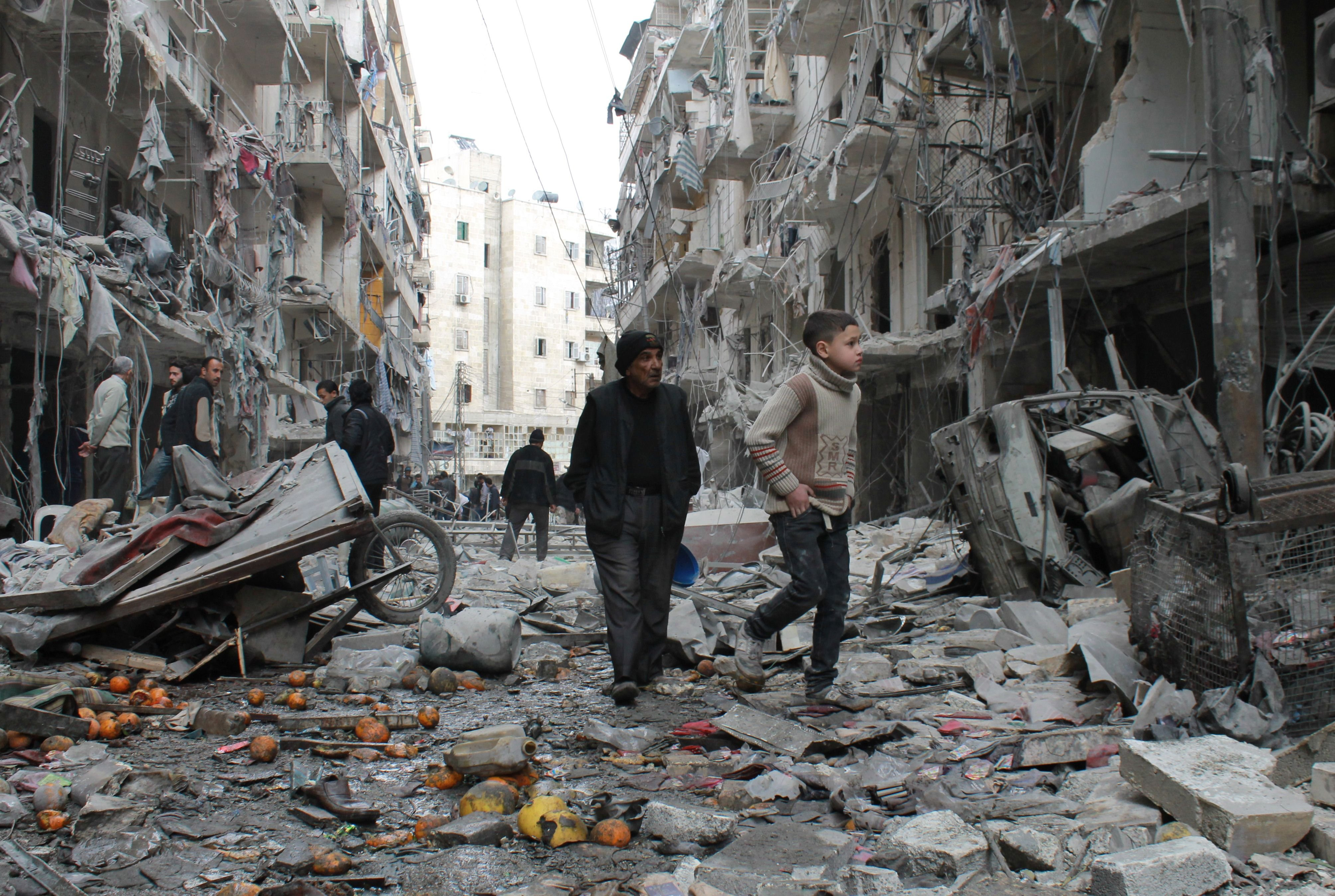 An elderly Syrian man and a child walk amidst debris in a residential block reportedly hit by an explosives-filled barrel dropped by a government forces helicopter on March 18, 2014 in Aleppo.