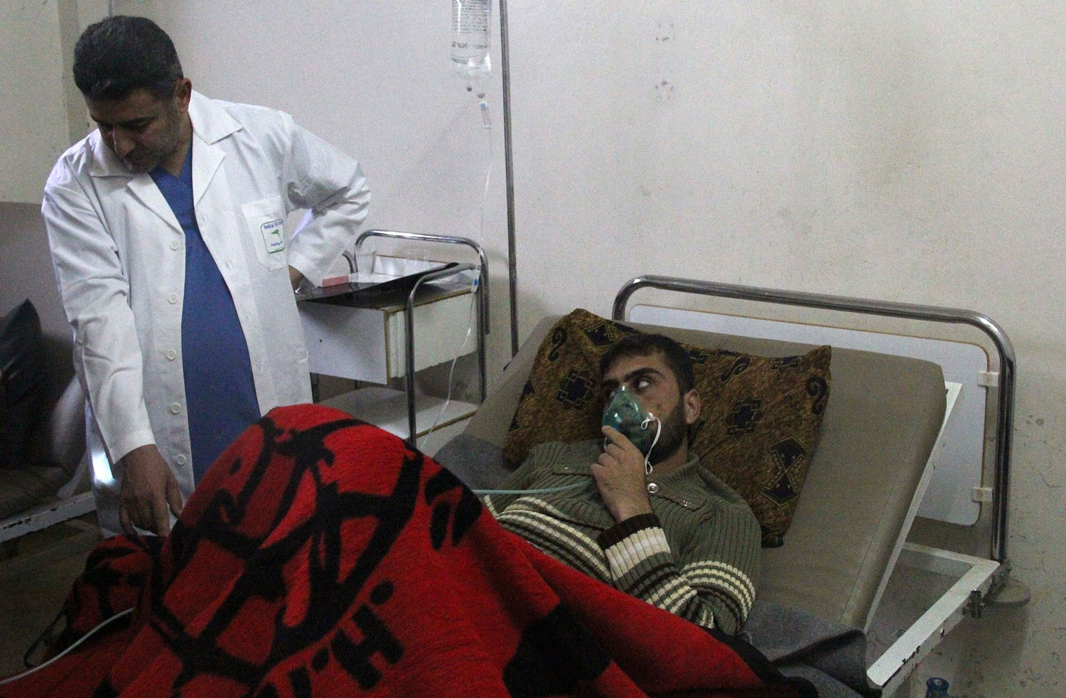 A man, affected by what activists say was a gas attack, breathes through an oxygen mask inside a field hospital in Kfar Zeita village in the central province of Hama, April 12, 2014.