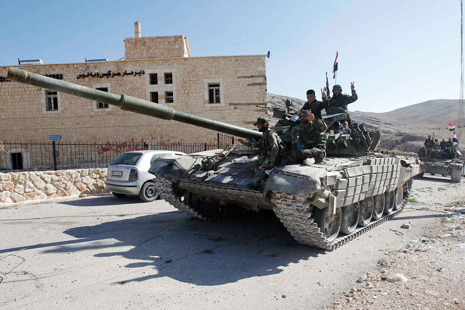 Soldiers loyal to Syria's President Bashar Assad gesture from their tank, as they pass Mar Bacchus Sarkis monastery, in Maaloula village, northeast of Damascus, after taking control of the village from rebel fighters, April 14, 2014.