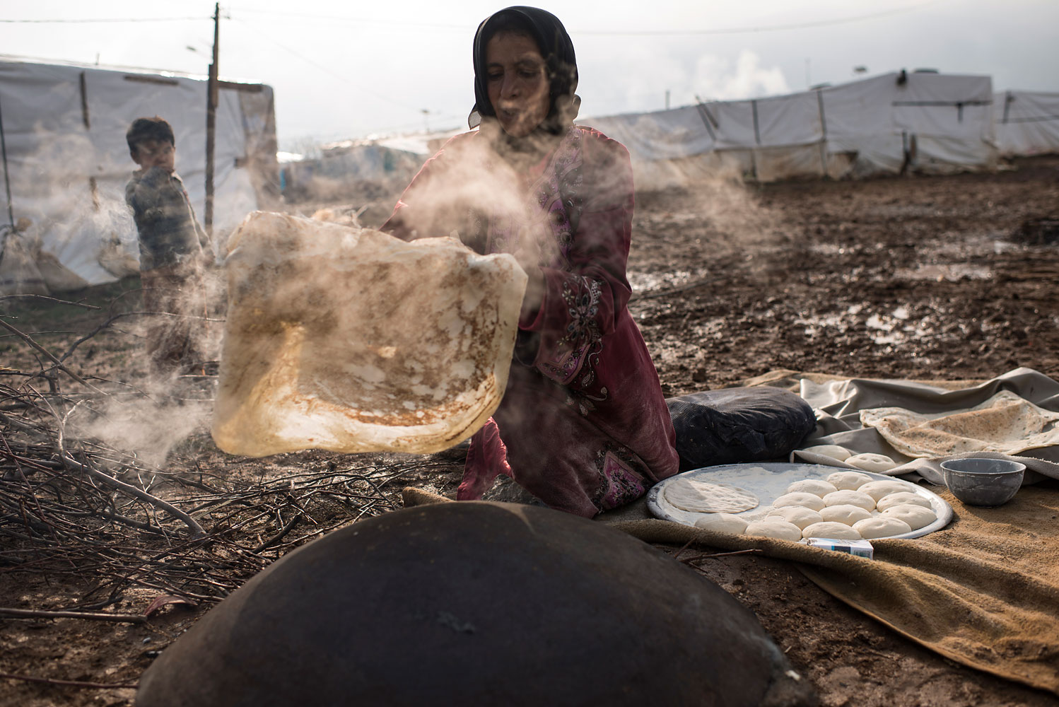 "Nafat, 45, from Homs, bakes bread outside her shelter in Turbide, Bekaa Valley. She has been in Lebanon for more than a year, and feeds her family of 13 every morning. ""The bakery is too expensive,"" she says. ""I learned to bake by watching my neighbours."