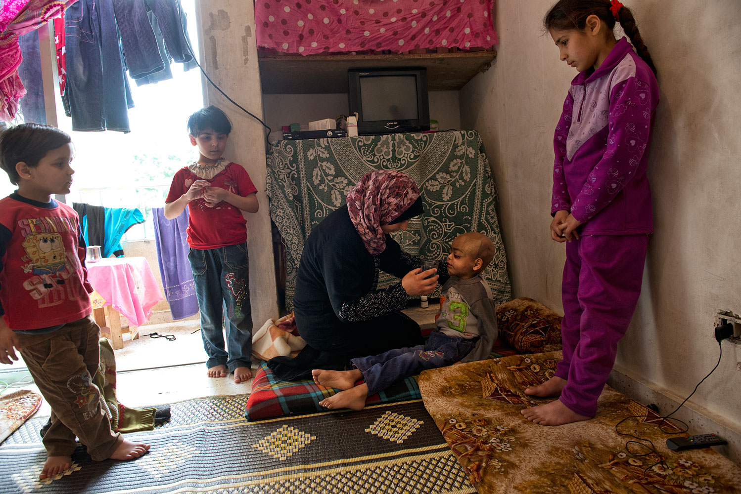 "Feryal, 29, gives water to Zacharia, her four-year-old son, in the apartment they live in in Halat. He is dying of cancer. In Syria, the trip to hospital became too dangerous. ""I was afraid,"" said Feryal. By the time they reached Lebanon, the cancer had spread to his brain, she says, adding: ""I failed him."""