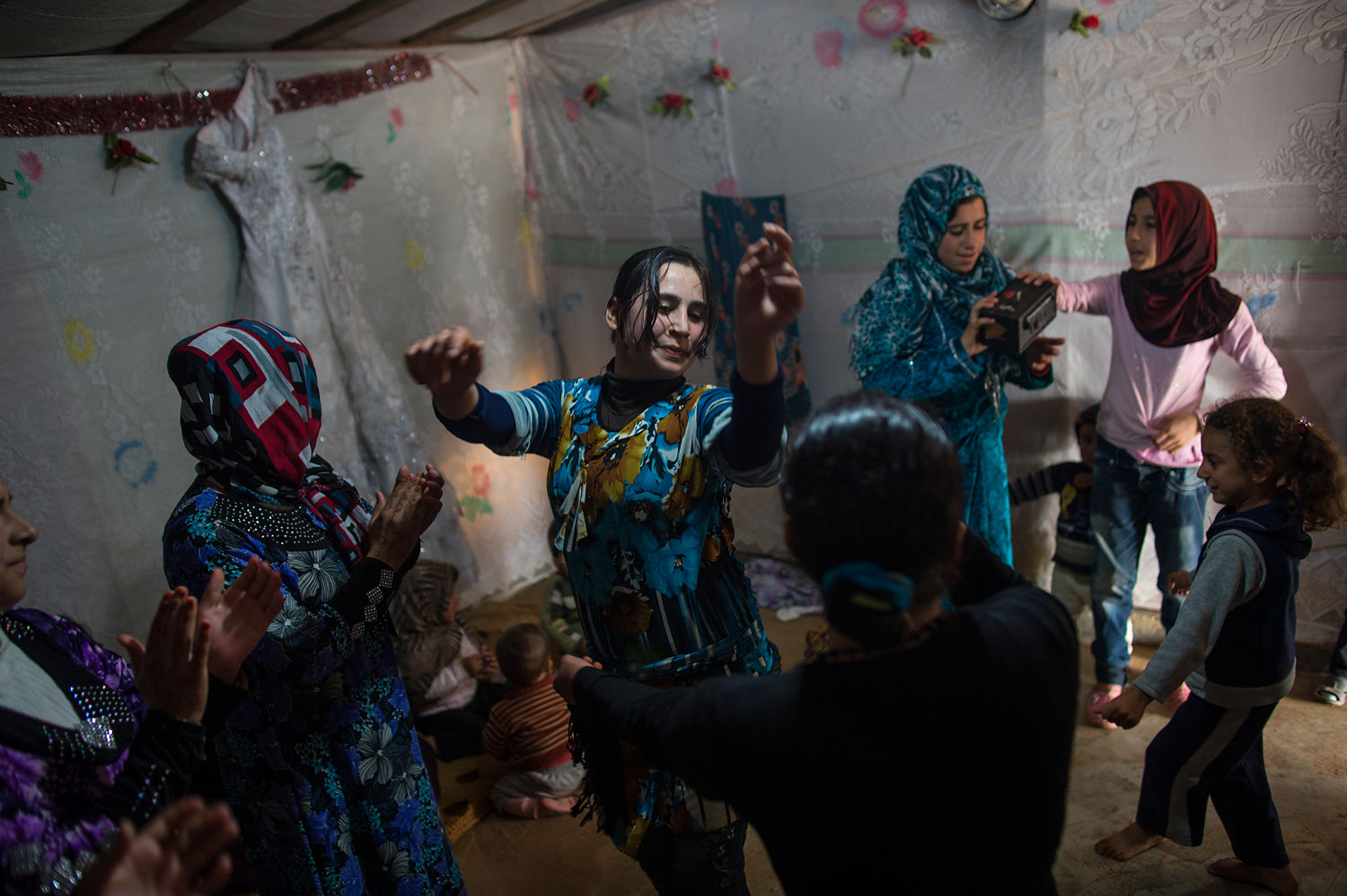 Female Syrian refugees dance around at a wedding celebration in a refugee camp in Marj El-Khokh, in Marjaayoun. The bride, Yousra, 16, (not shown) was marrying Ahmed, 21, from East Ghouta, Syria. The father of the groom spoke about the wedding  we want to create life out of death and from sadness we want to create happiness.