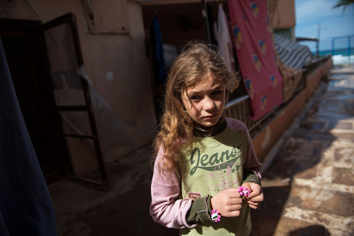 Syrian refugee Ranya, 10, from the Idlib countryside, stands outside her family's room in the Nour resort, a collective shelter that houses roughly 500 Syrian refugees in Tripoli, in North Lebanon. Ranya and her family fled Idlib about one year ago after the bombing intensified. She has been out of school for three years.
