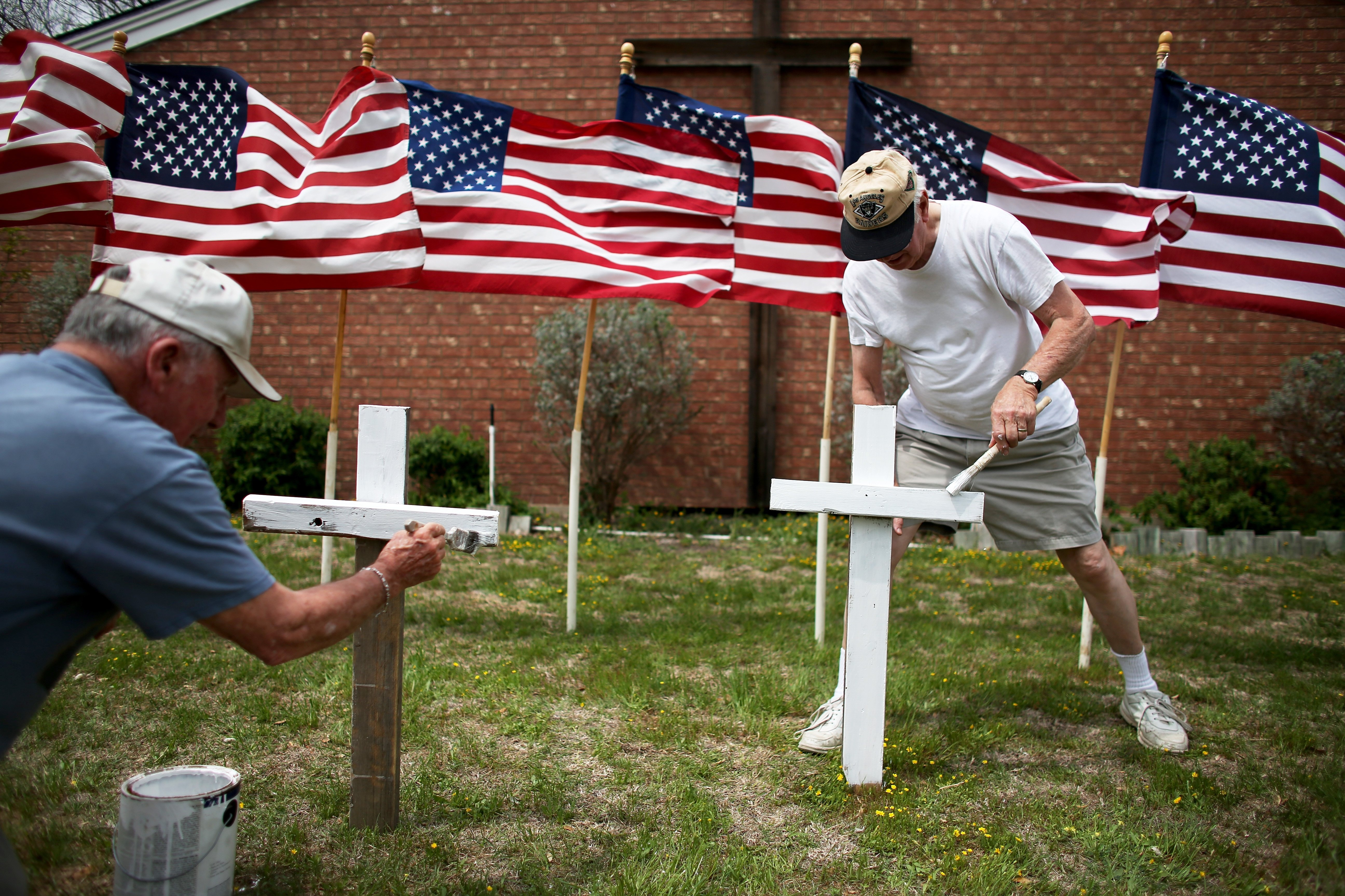 From left: Bob Gordon and Bob Butler paint crosses they placed in front of 16 American flags as they build a memorial in front of Central Christian Disciples of Christ church for the victims of yesterdays shooting at Fort Hood on April 3, 2014 in Killeen, Texas.