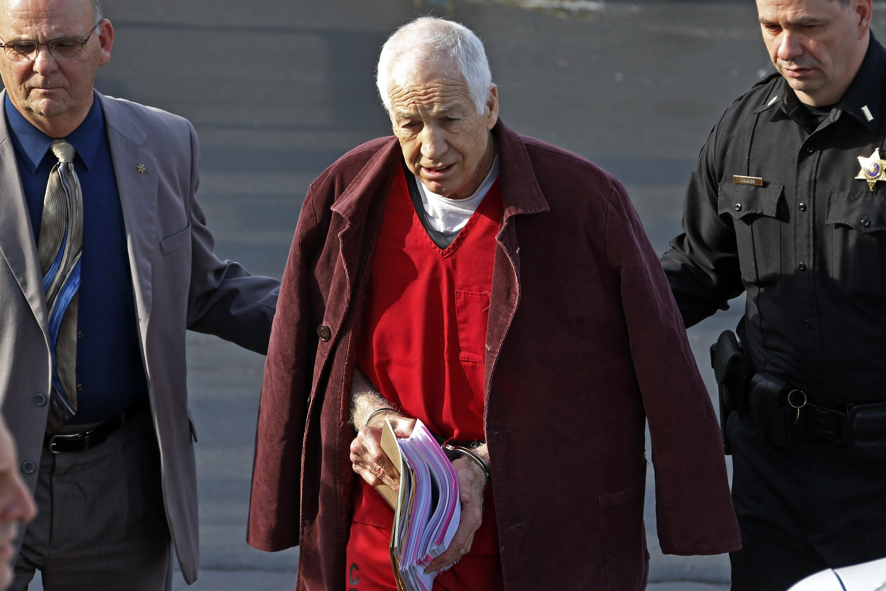 Former Penn State University assistant football coach Jerry Sandusky, center, leaves the Centre County Courthouse after attending a post-sentence motion hearing in Bellefonte, Pa., Jan. 10, 2013.