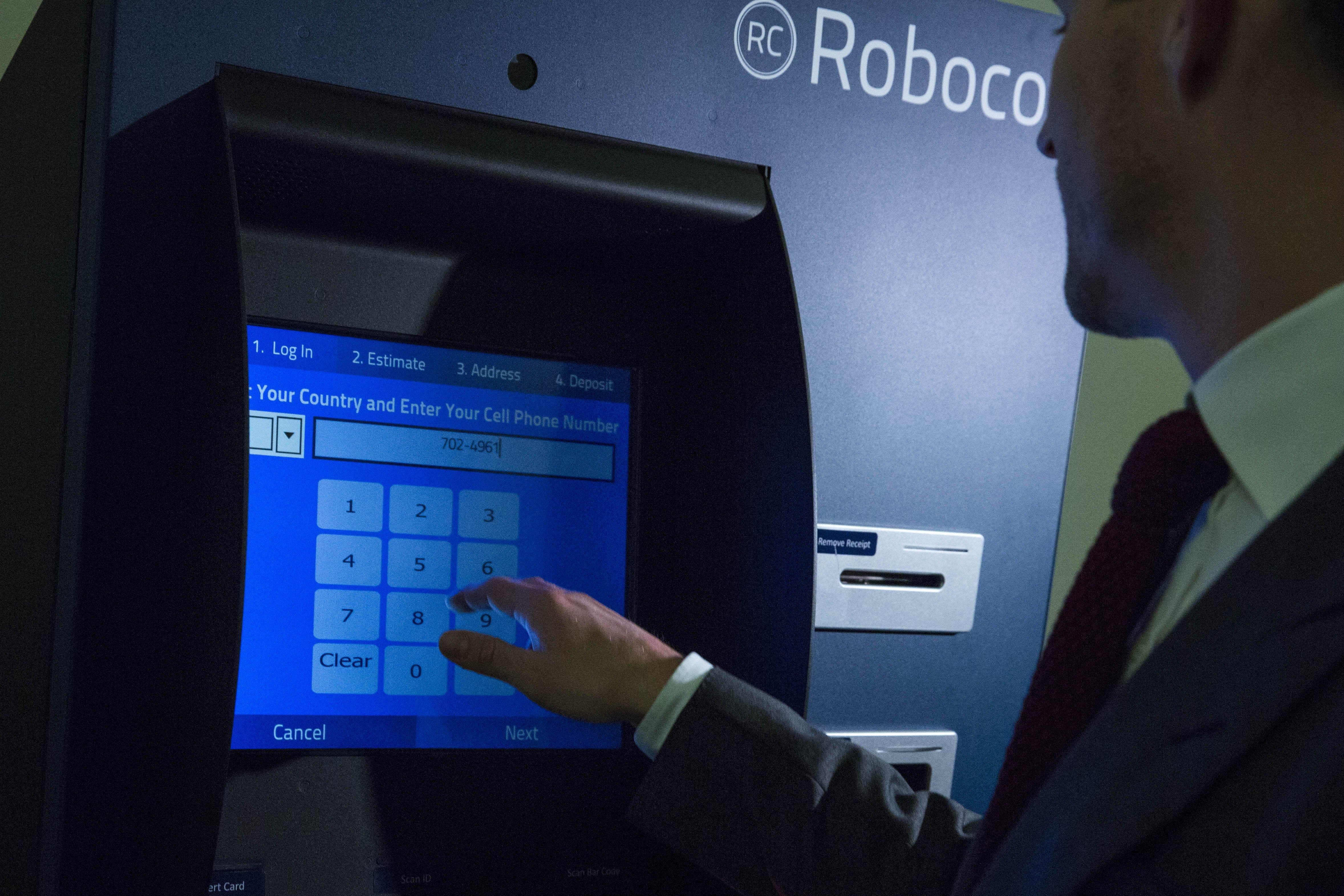 Robocoin CEO and co-founder Jordan Kelley uses the Robocoin Bitcoin ATM, during a demonstration of the ATM in the Rayburn House Office Building on Capitol Hill, April 8, 2014 in Washington.