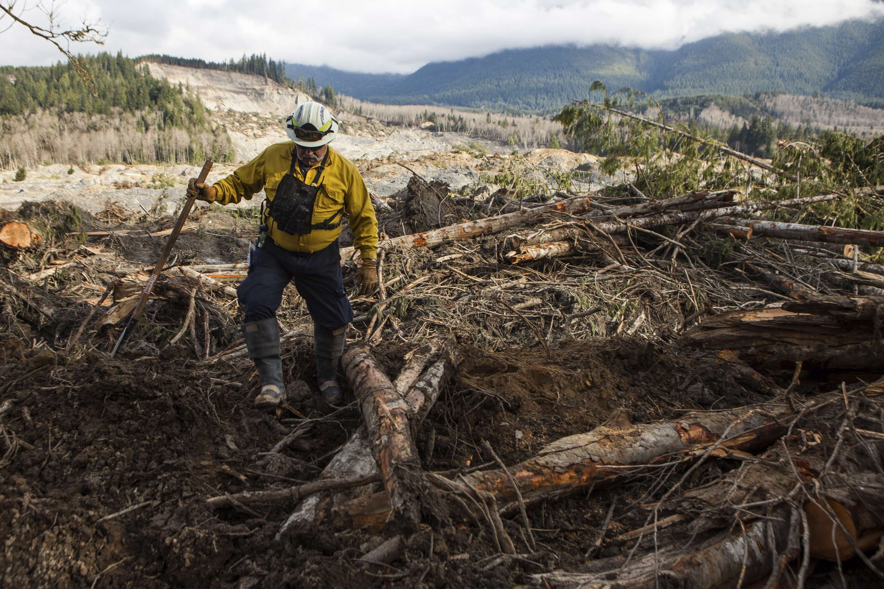Benton County Assistant Fire Chief Jack Coats makes his way over debris left by a mudslide in Oso, Wash., April 2, 2014.