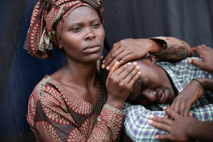 Rwandans impacted by the genocide comfort each other during a commemoration ceremony in Kigali on April 7
