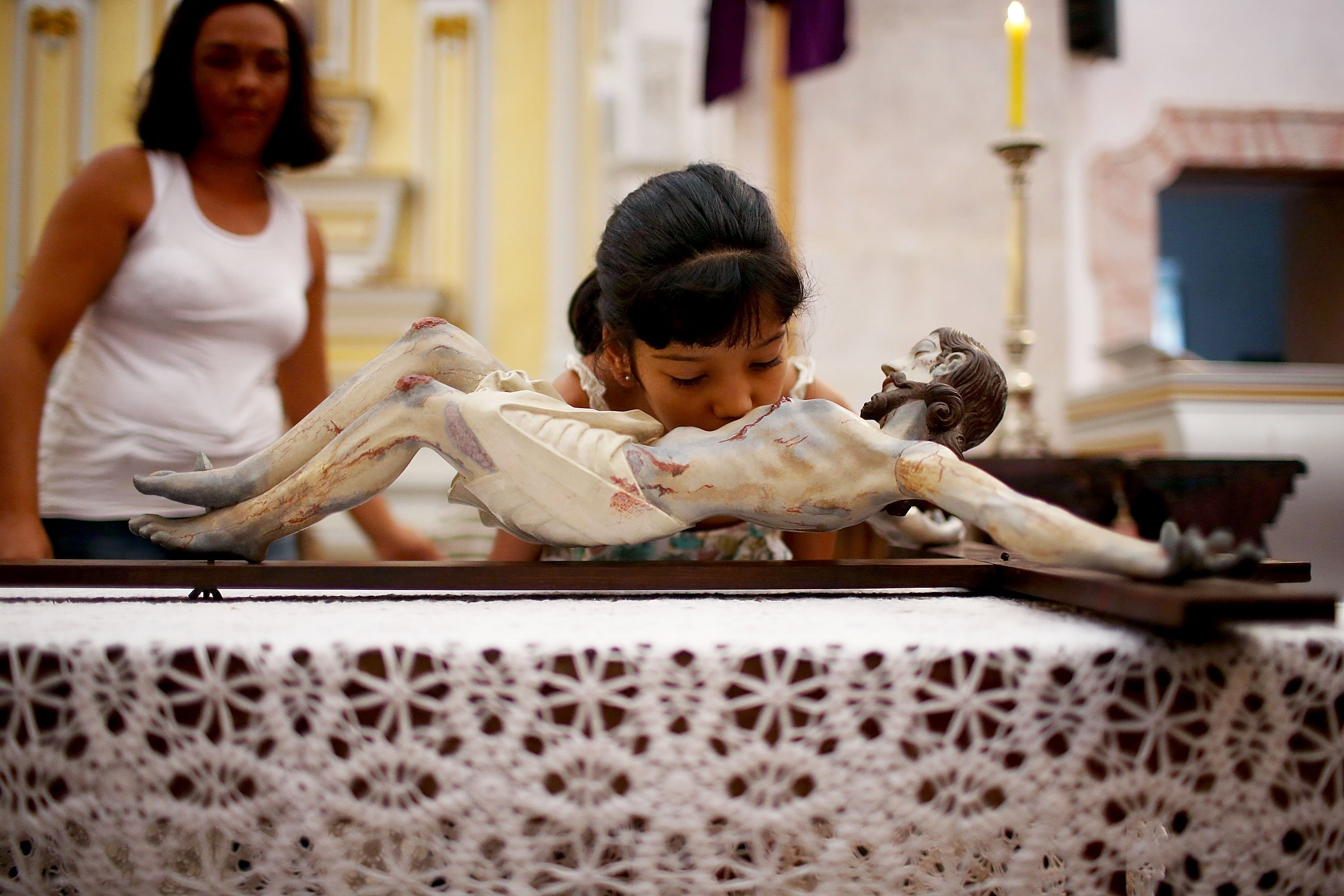 A young worshiper kisses a statue of Christ hanging on the cross during Holy Week festivities on April 18, 2014 in Paraty, Brazil.