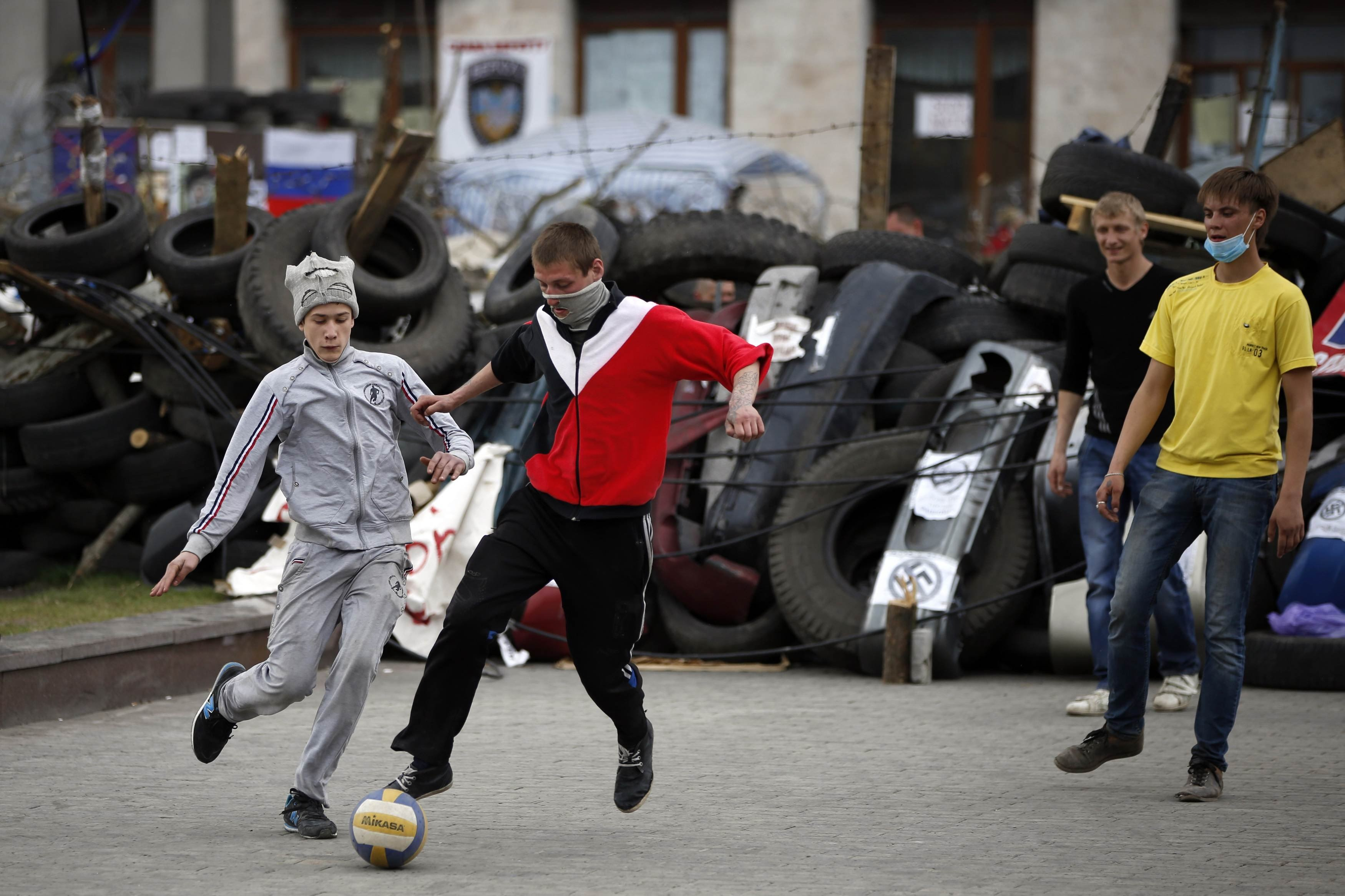 Pro-Russian protesters play soccer in front of a barricade outside a regional government building in Donetsk, eastern Ukraine April 19, 2014.