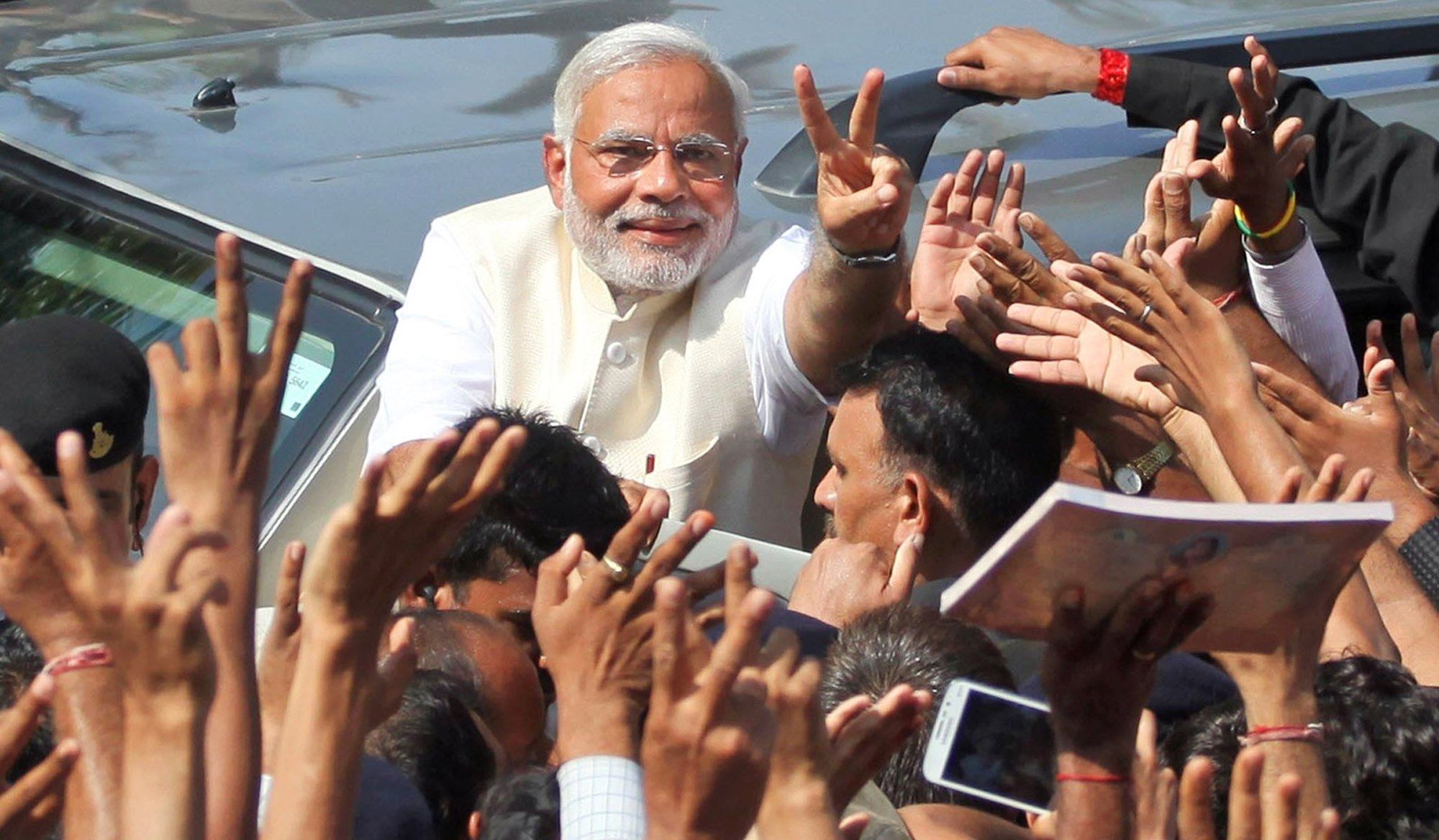 India's main opposition Bharatiya Janata Party's prime-ministerial candidate, Narendra Modi, displays the victory symbol to supporters after casting his vote in Ahmedabad, India, on  April 30, 2014
