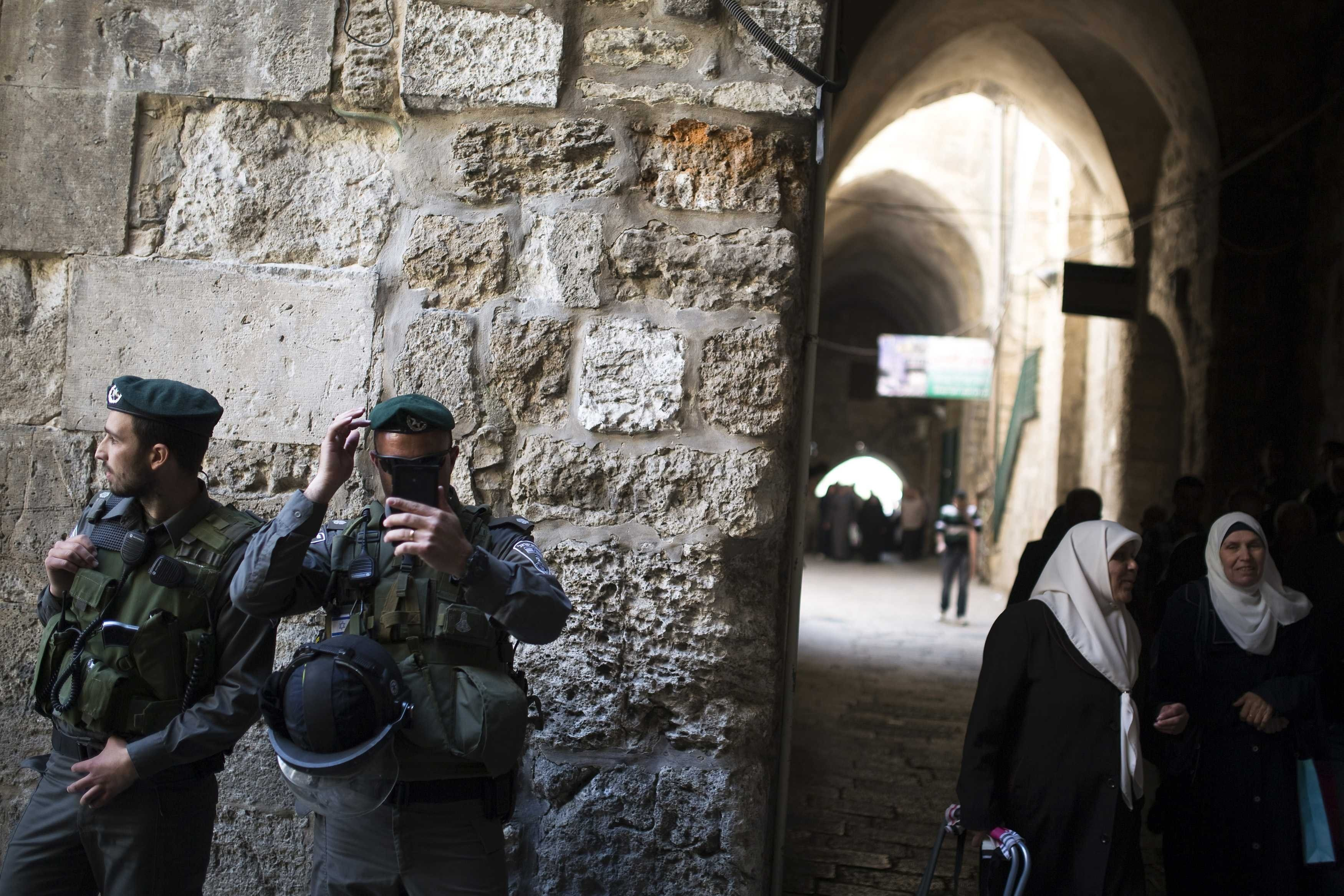 Palestinian women walk near Israeli border policemen after Friday prayers in Jerusalem's Old City April 4, 2014.