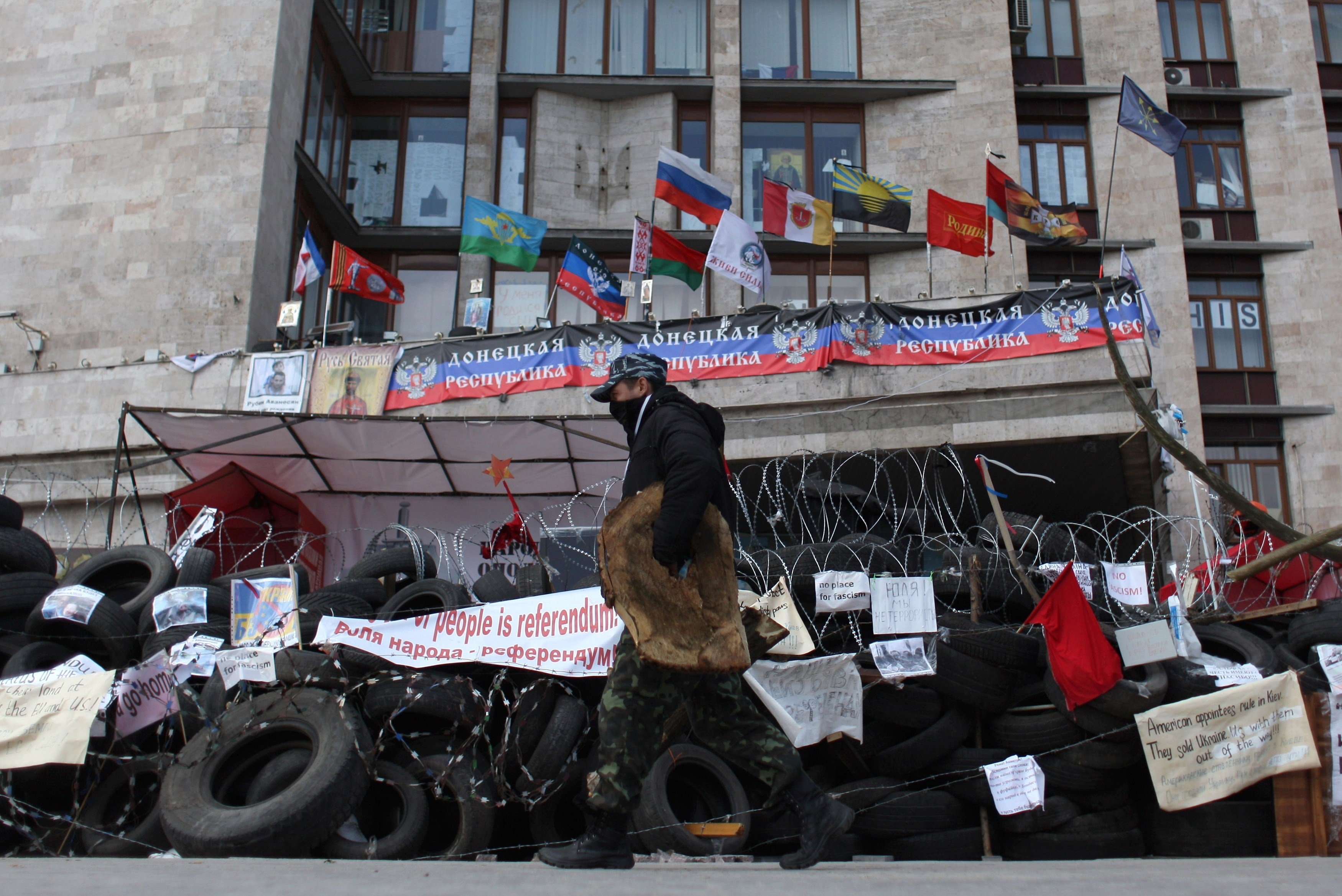 A pro-Russian activist walks in front a barricade set up outside the regional administrative building in the eastern Ukrainian city of Donetsk on April 21, 2014.