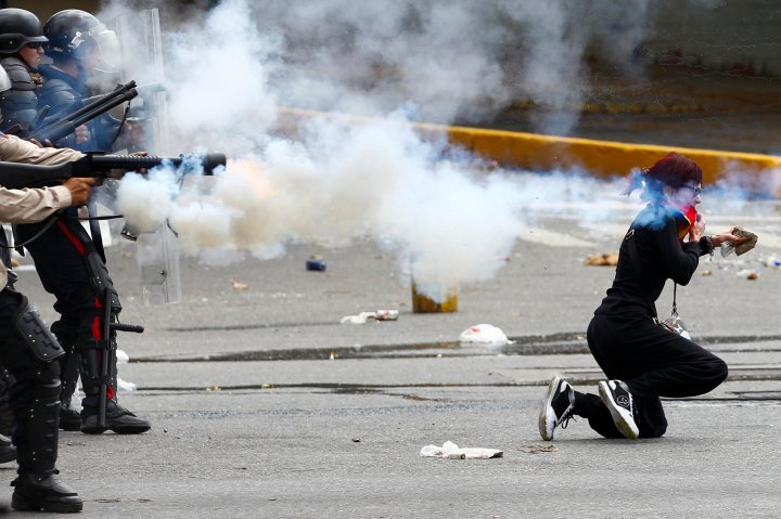 An antigovernment protester ducks for cover as Venezuelan police fire tear gas during riots in Caracas