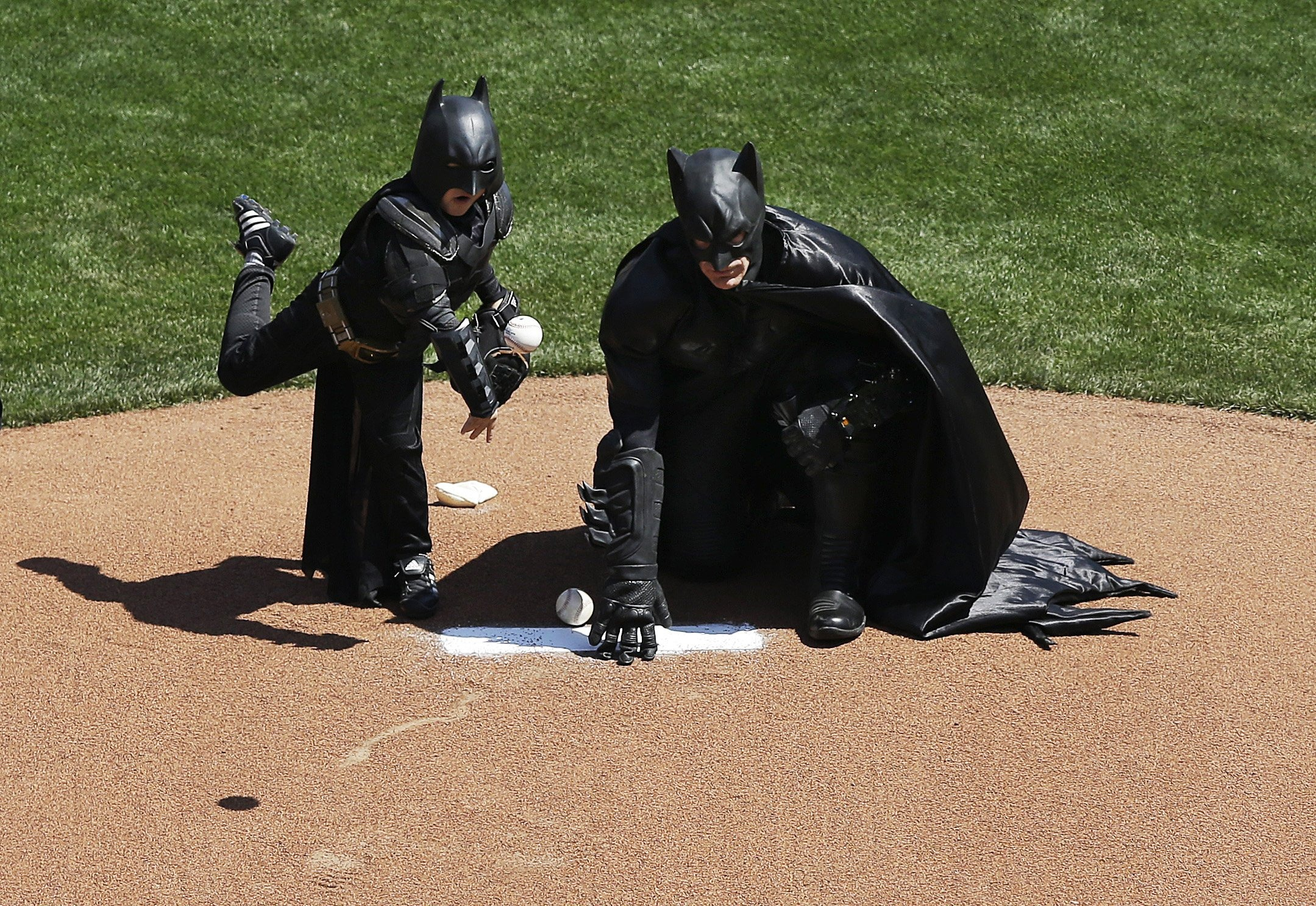 Miles Scott, dressed as Batkid, left, throws the ceremonial first pitch next to Batman before an opening day baseball game between the San Francisco Giants and the Arizona Diamondbacks in San Francisco, April 8, 2014.