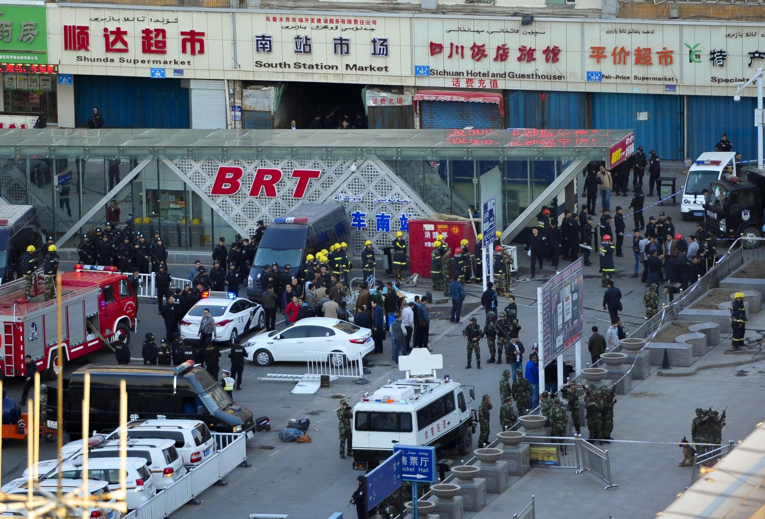 Security personnel inspect the explosion site outside Urumqi South Railway Station in Urumqi, northwest China's Xinjiang Uighur Autonomous Region, on April 30, 2014