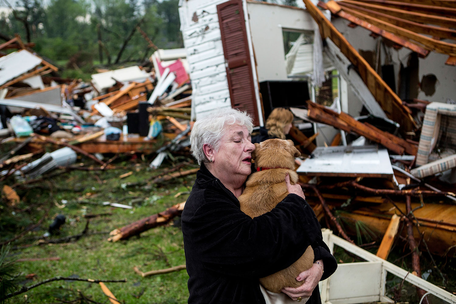 Constance Lambert embraces her dog after finding it alive when returning to her destroyed home in Tupelo, Miss., April 28, 2014.