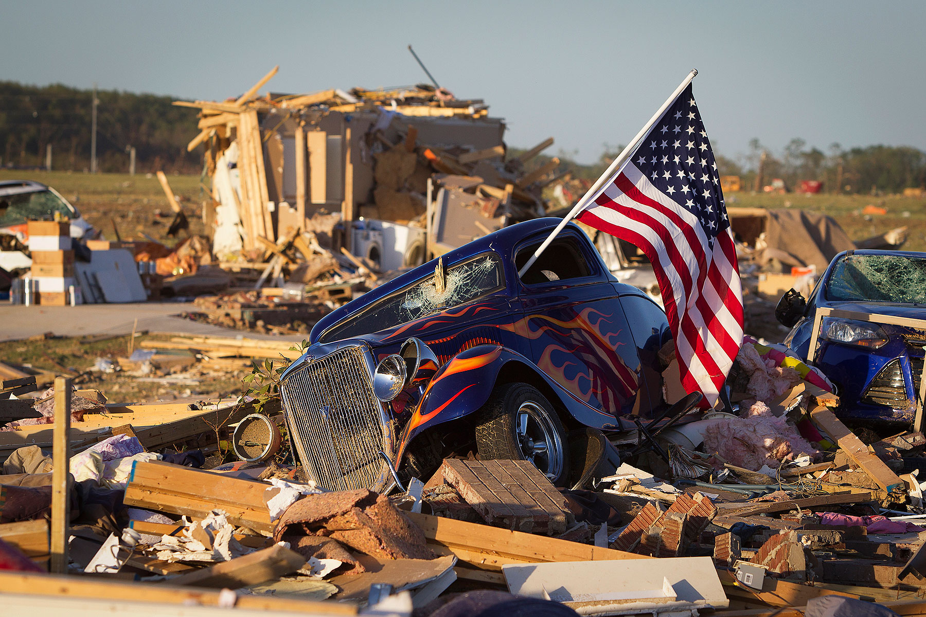 A U.S. flag sticks out the window of a damaged hot rod car in a suburban area after a tornado near Vilonia, Arkansas April 28, 2014