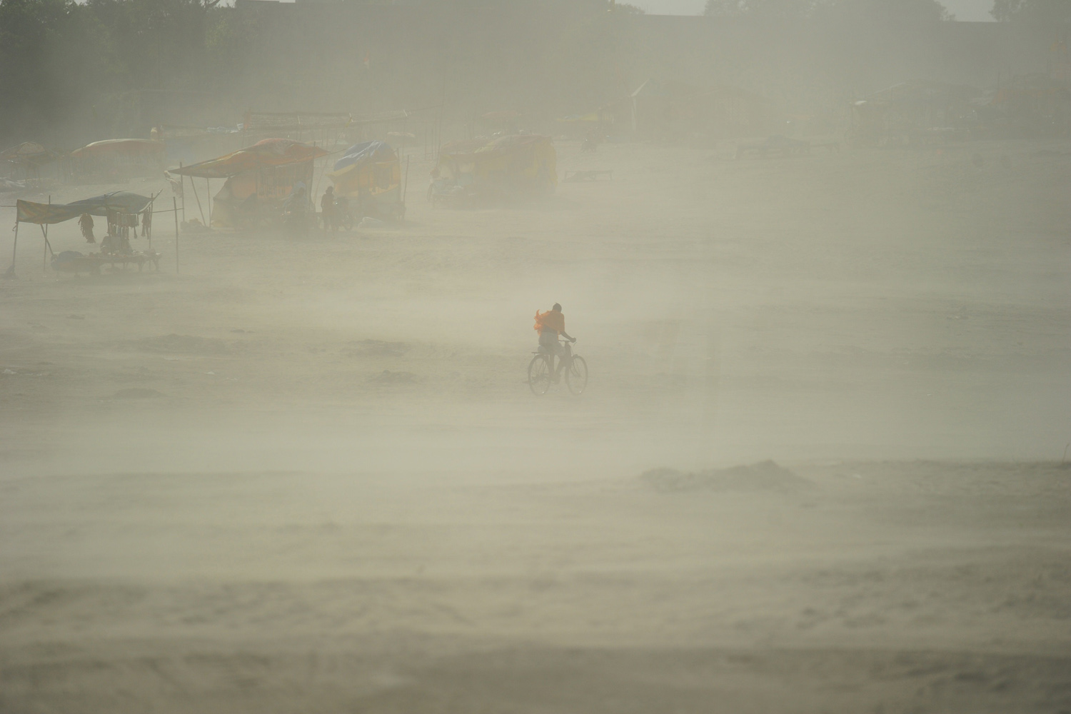 Apr. 5, 2014. A Hindu devotee rides his bicycle through a dust storm at the Sangam after taking a holy dip at the confluence of the rivers Ganges, Yamuna and mythical Saraswati, in Allahabad.