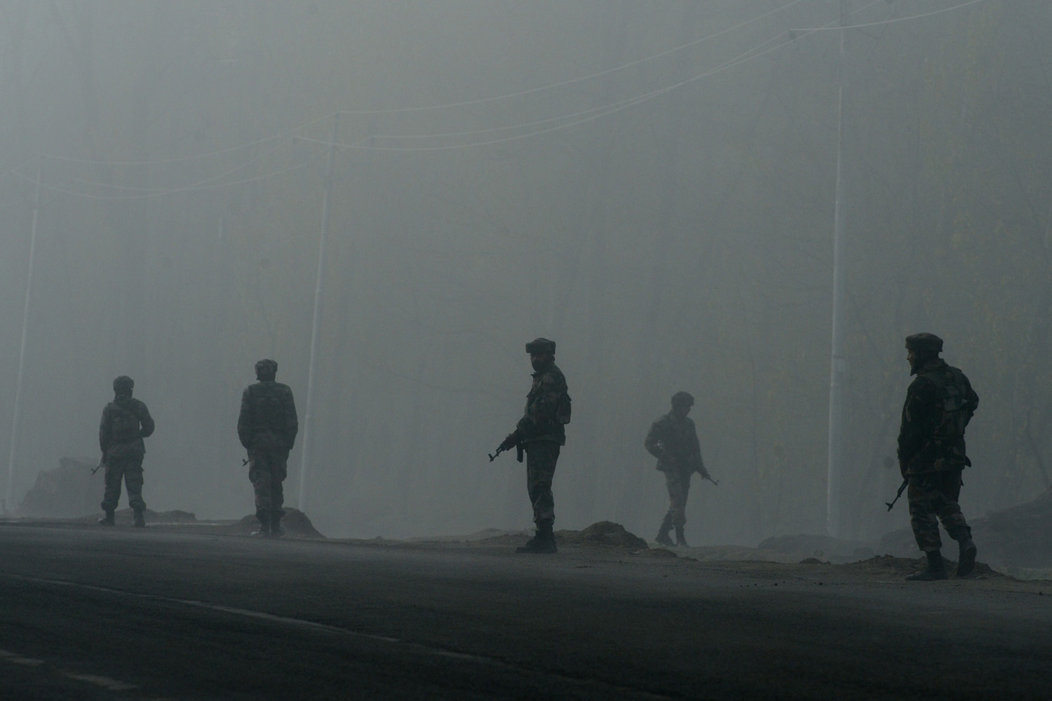 Apr. 24, 2014. Indian army soldiers patrol along a roadside amongst heavy fog outside a polling station in Sangam.