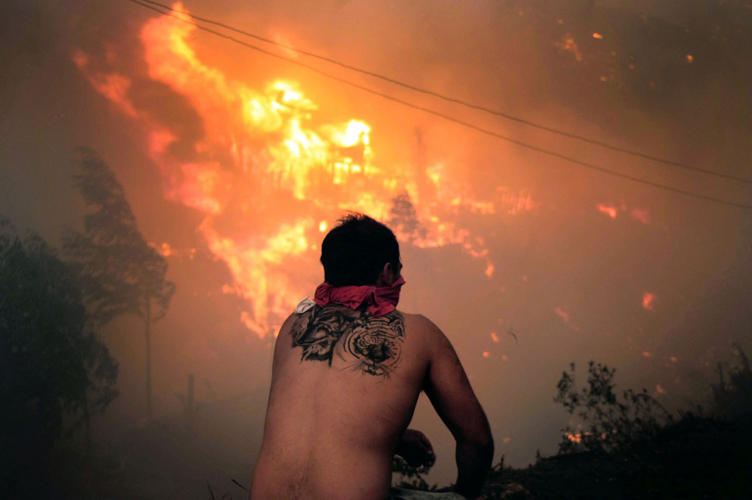 A local stares at houses in flames, April 13, 2014.