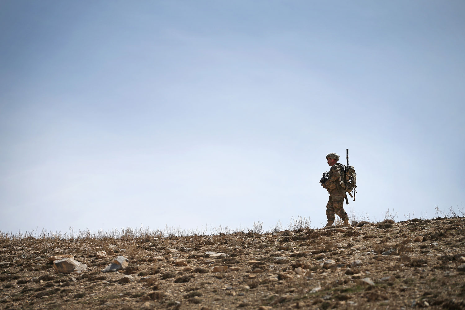 U.S. soldier walks along a ridgeline during a patrol up a mountainside near Forward Operating Base Shank on March 31, 2014 near Pul-e Alam, Afghanistan.