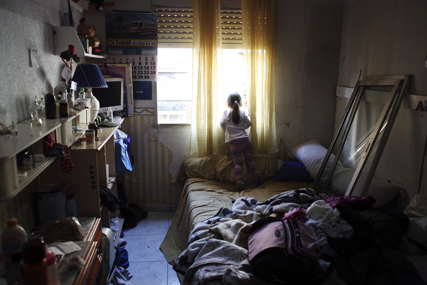 April 11, 2014. Dayana Chasi Saavedra, 3, looks through the window after news that their eviction was not going to be carried out, in Madrid, Spain.