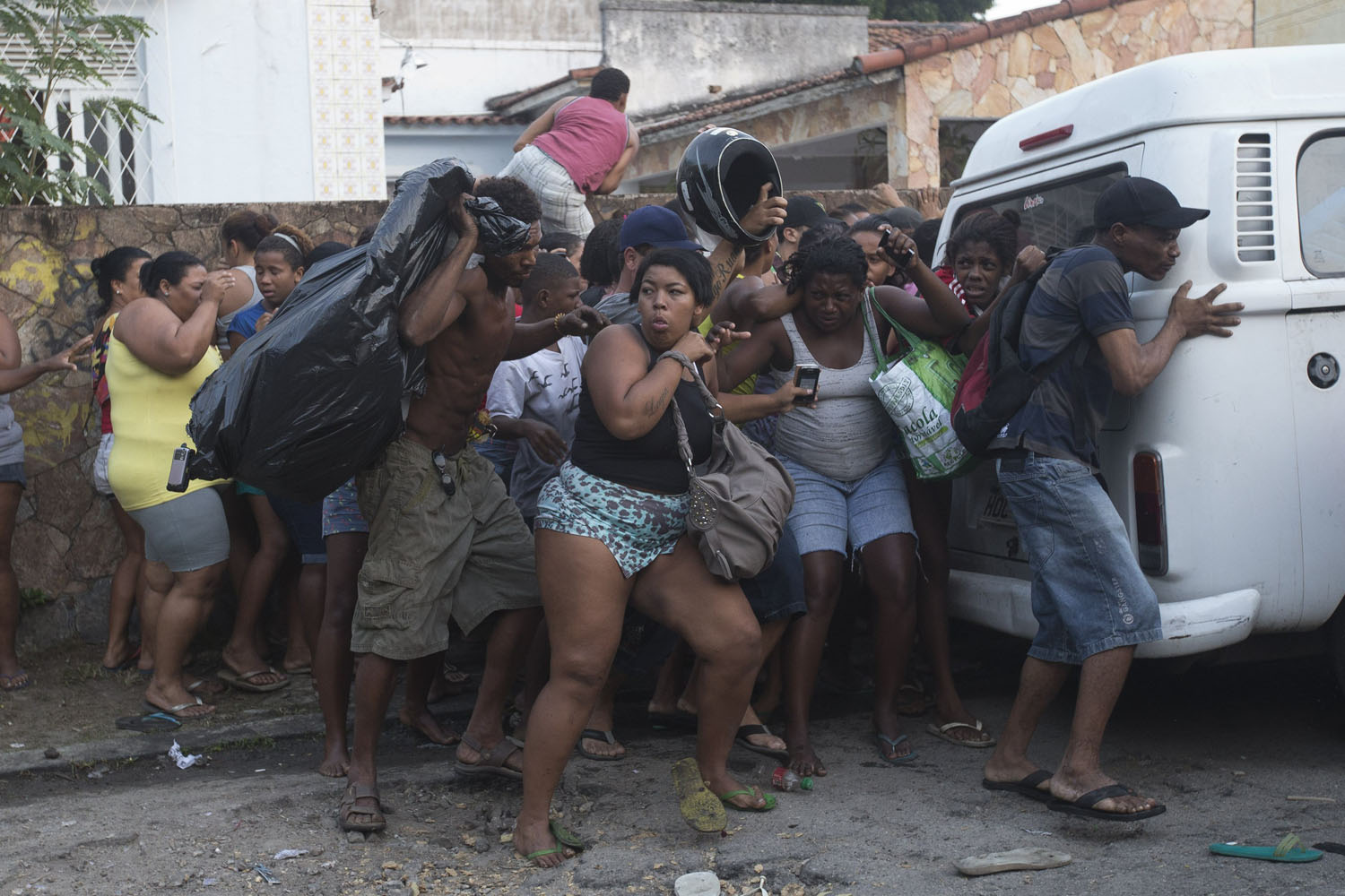 April 11, 2014. Squatters take cover from stun grenades and tear gas during an eviction in Rio de Janeiro, Brazil,