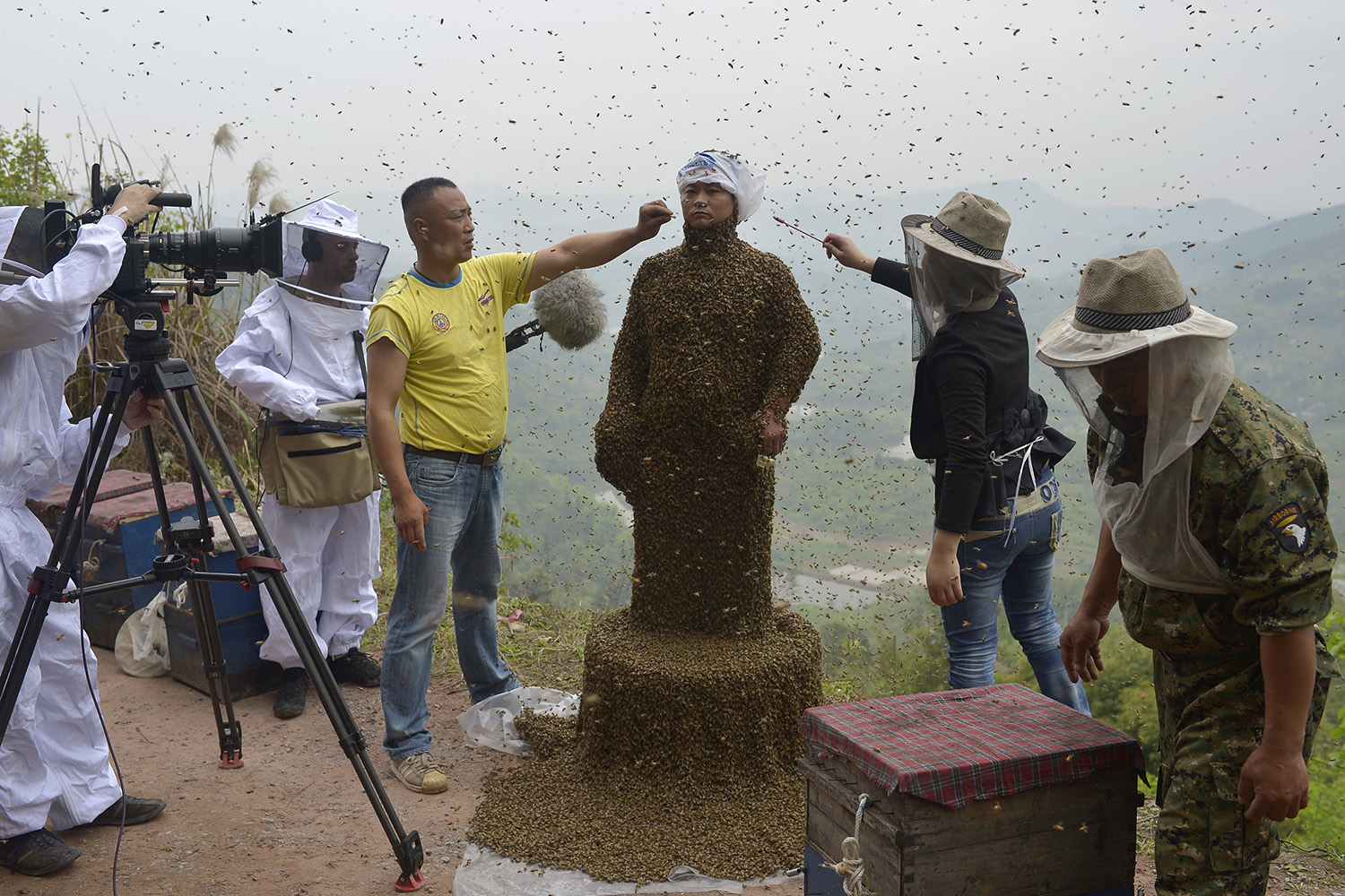 April 9, 2014. Assistants use burning incense and cigarettes to drive away bees from the face of She Ping, a 34-year-old beekeeper, during an attempt to cover his body with bees, in Chongqing municipality, China.