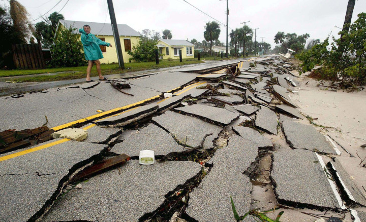 #12 Hurricane Frances - A man walks down Indian River Road, Sept. 5, 2004 in Jensen Beach, Fla. The road was destroyed after Hurricane Frances pounded the eastern coast of Florida overnight leaving many residents without electricity. Frances broke the $10 billion damage barrier.