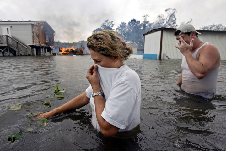#9 Hurricane Rita - Rose Machado, left, walks in waist high floodwater as her neighbors' trailer burns in Lafitte, La., after Hurricane Rita passed through the area, Sept. 24, 2005. Coming so soon after Hurricane Katrina, Rita is often forgotten, but it caused $11.8 billion in damages.