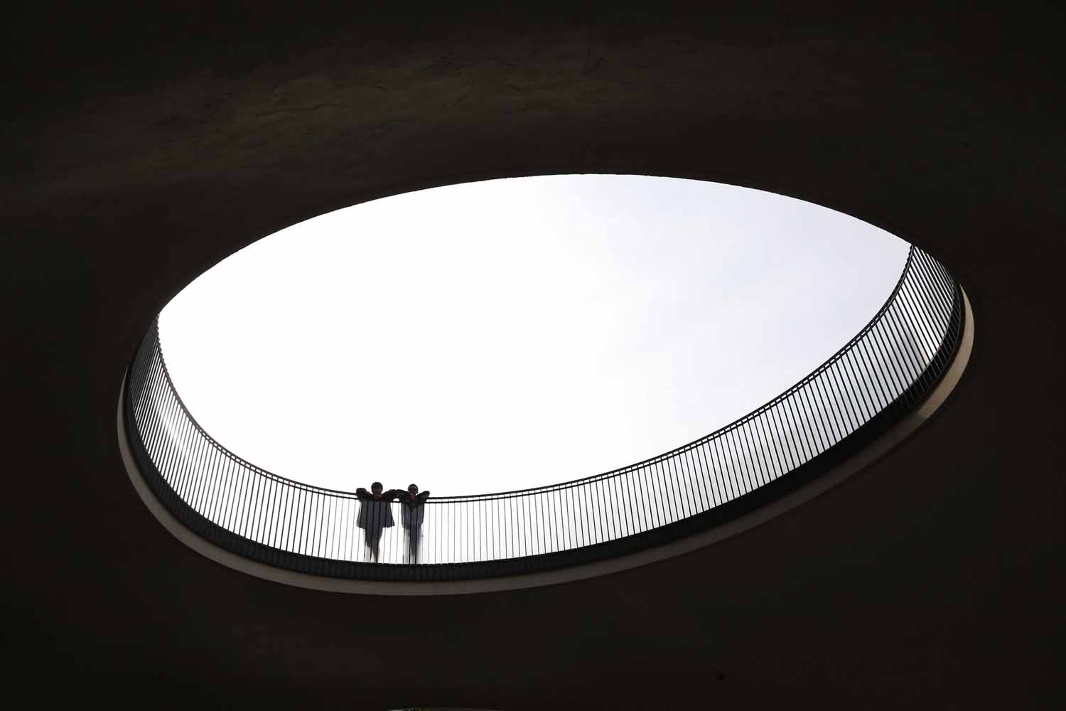 May 28, 2014. Men look in a hole in front of a building in Tokyo, Japan.