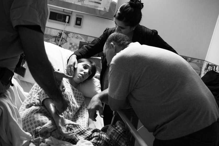 Gena's parents, Rich and Sue, comfort her before she is wheeled out for surgery.