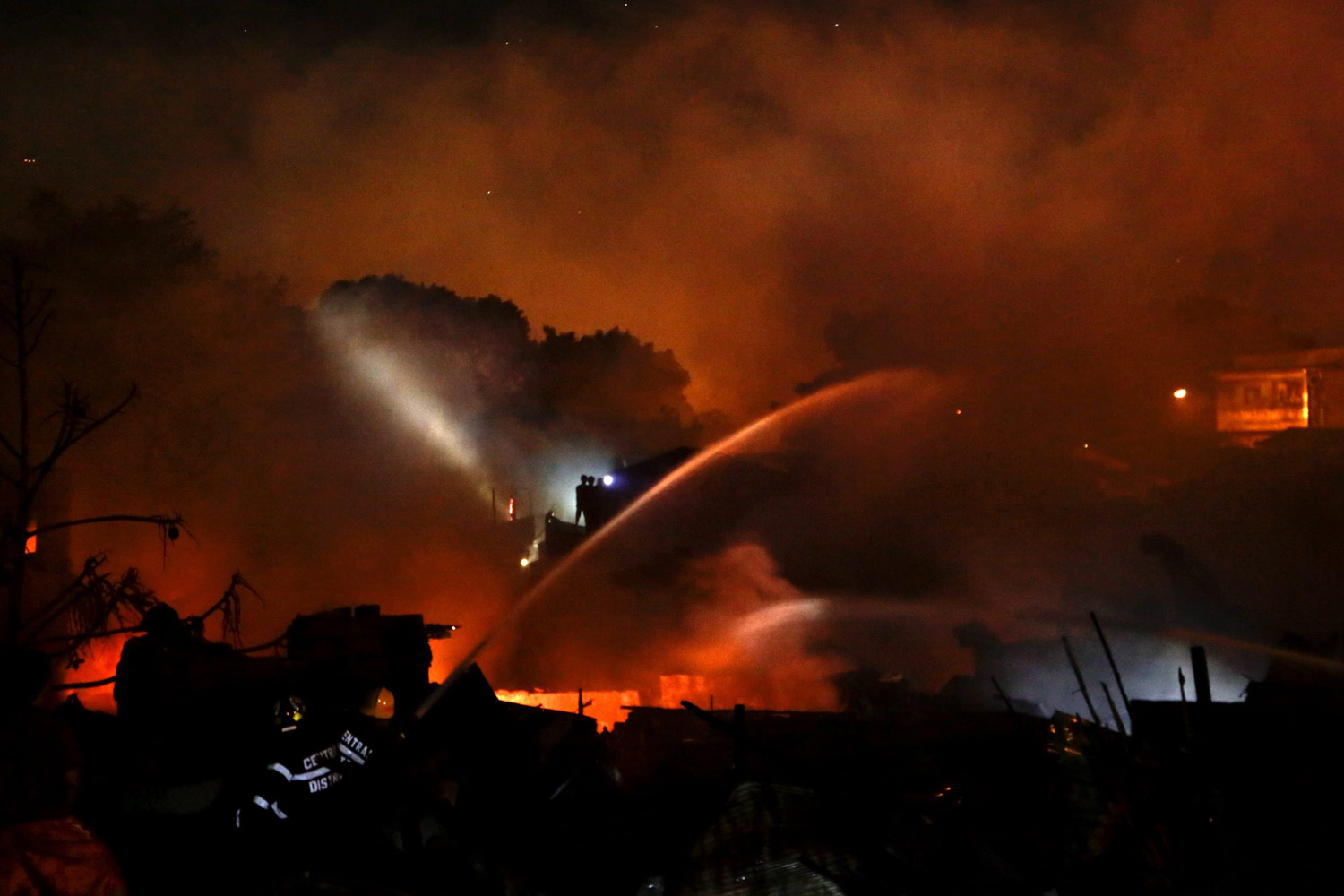 May 6, 2014. Filipino firemen use a water cannon to extinguish a fire in a residential slum area in Quezon City, east of Manila, Philippines.