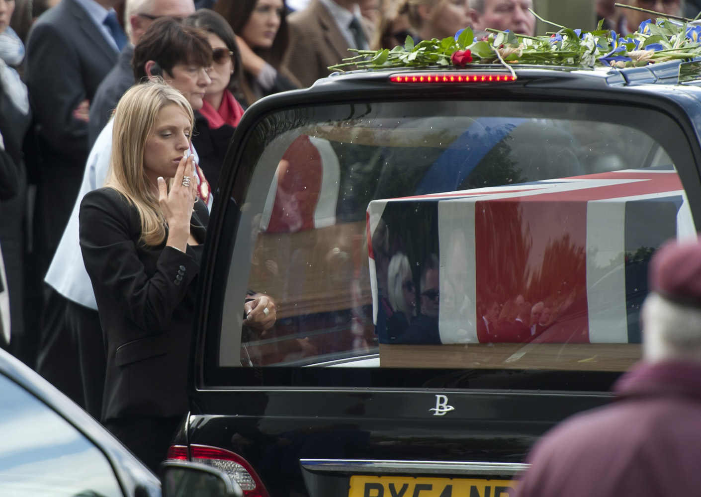 May 7, 2014. A mourner blows a kiss to a departed loved one after the repatriations of Capt Thomas Clarke, Warrant Officer Spencer Faulkner, Cpl James Walters, RAF Intelligence Officer Flt Lt Rakesh Chauhan and L/Cpl Oliver Thomas, who were killed in a helicopter crash on Apr. 26 in Afghanistan.