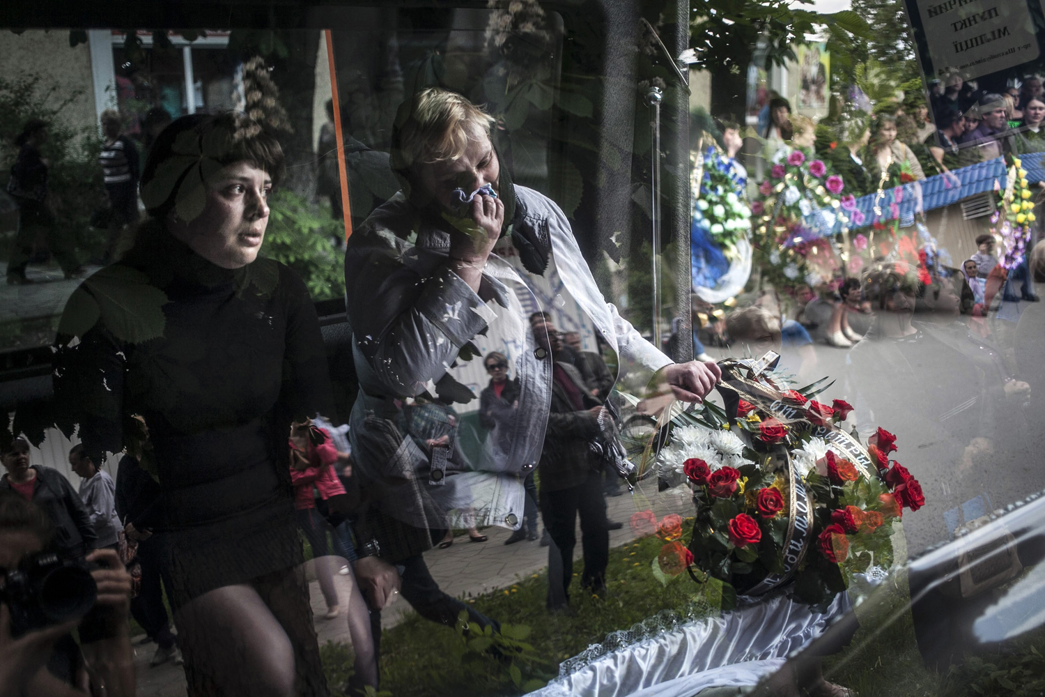 May 13, 2014. The mother (R) and wife (L) of Hyudych Vadim Yurievich cry during his funeral in the eastern Ukranian town of Krasnoarmisk,  Yurievich, a 39-year-old Ukrainian man, was reportedly killed in an incident involving Ukranian militia and pro-Russian supporters on May 11, during referendum voting.
